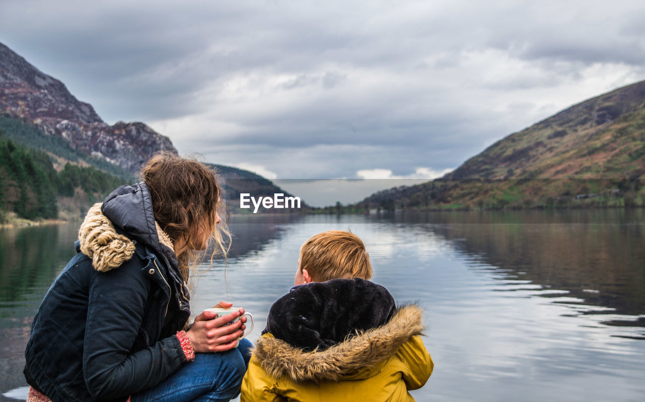 Woman And Child By Lake Against Mountain Range