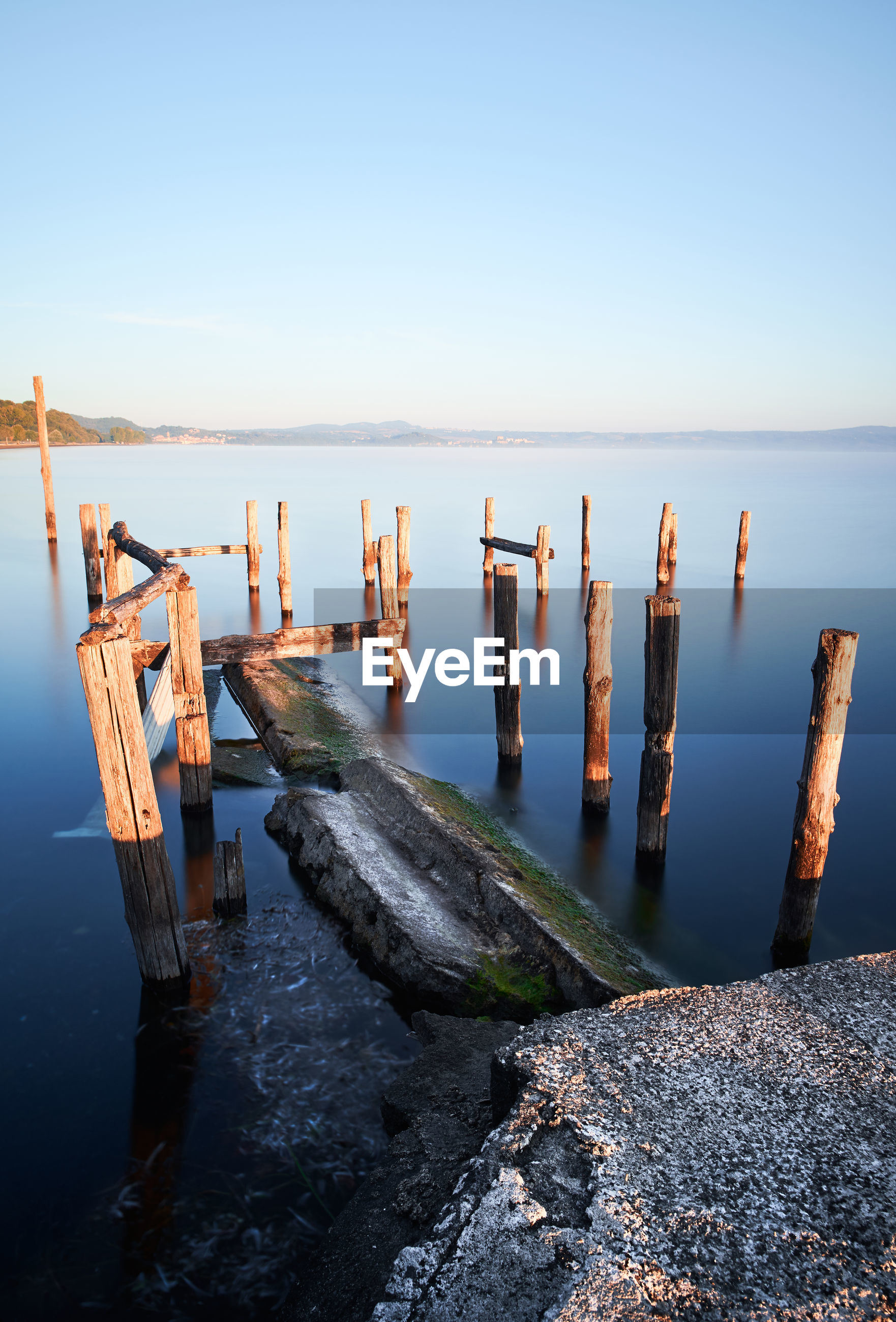Long exposure of bolsena lake with water and old pier with poles