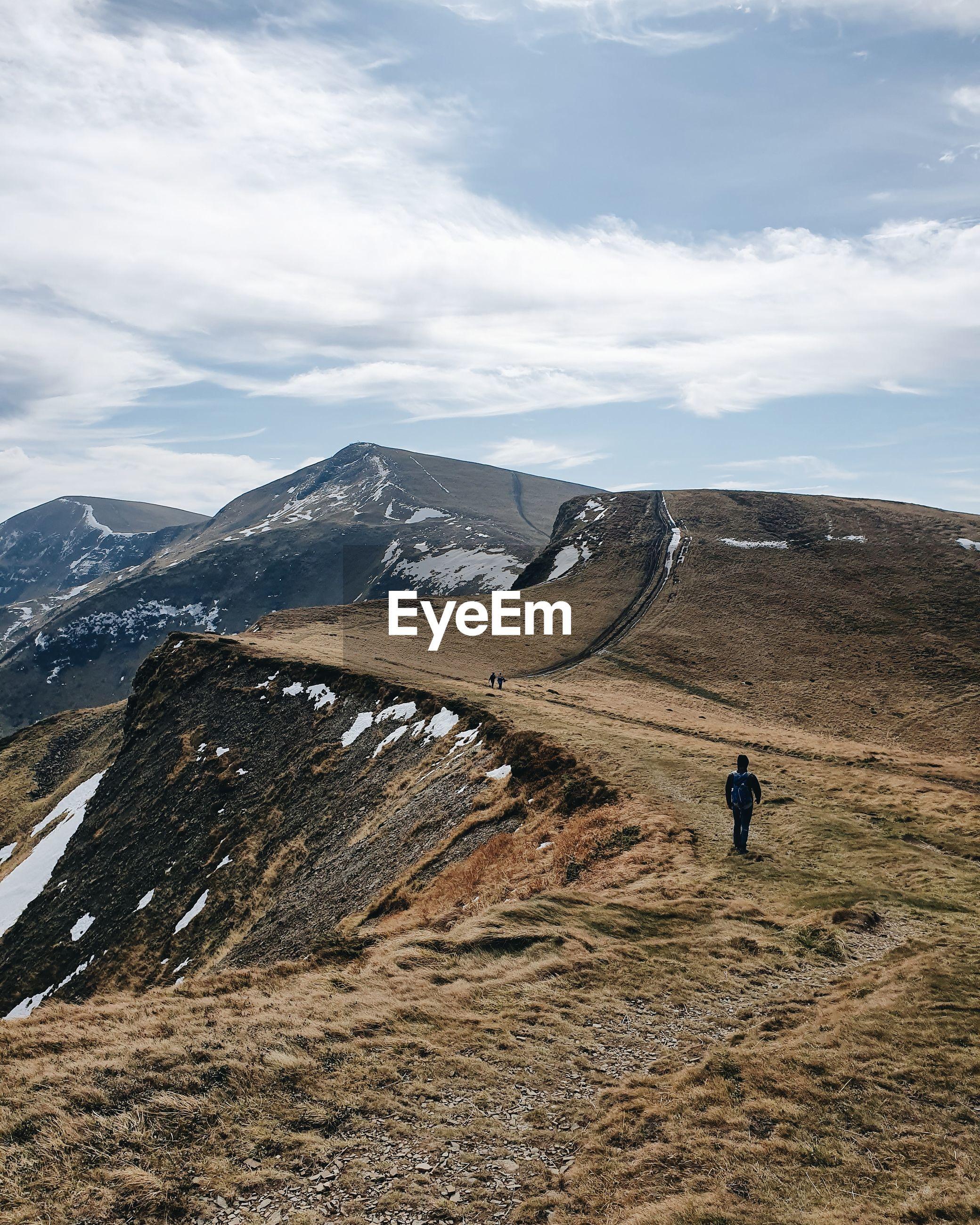 Rear view of man hiking at mountain