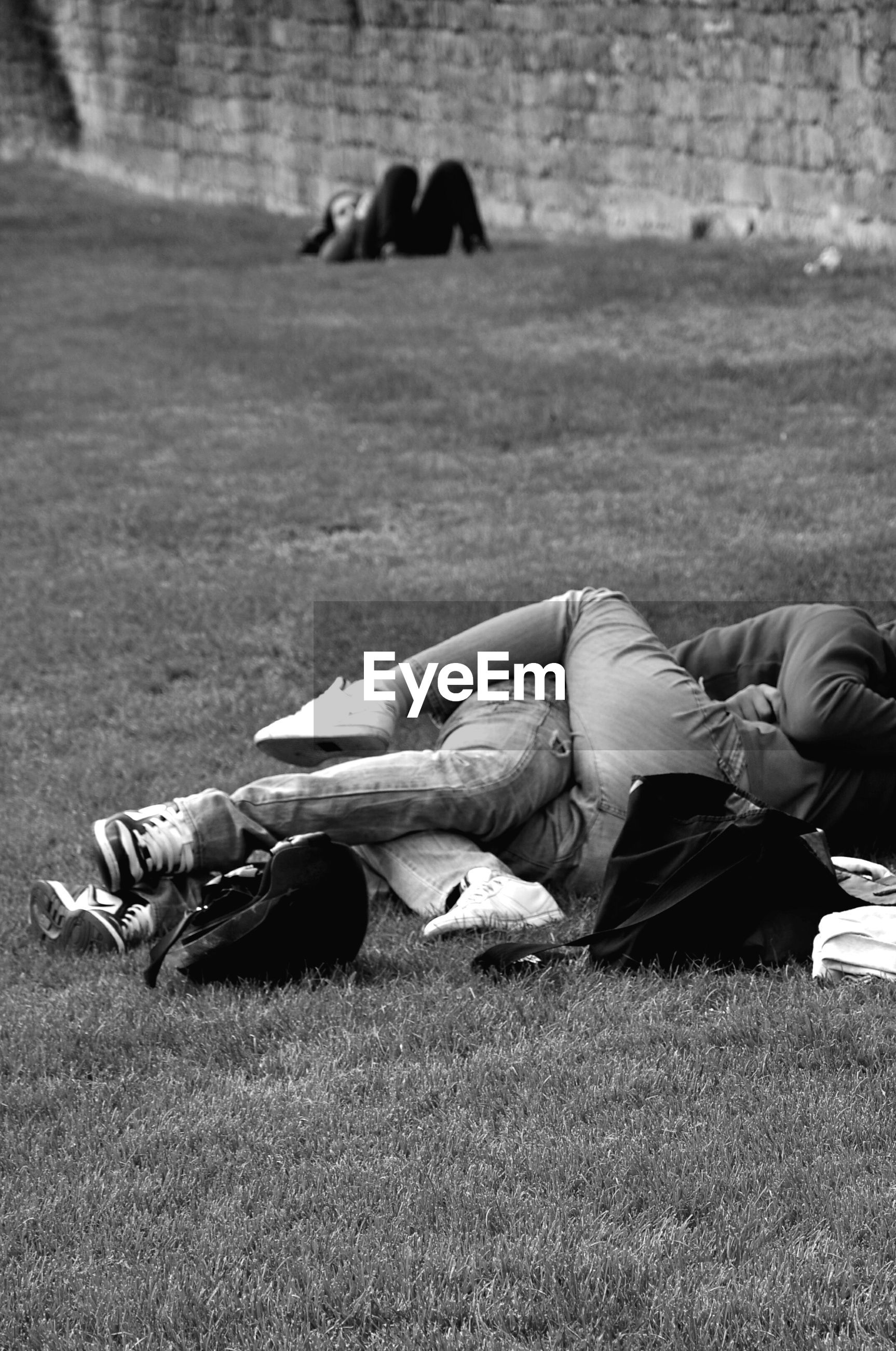 Couple lying on field at park