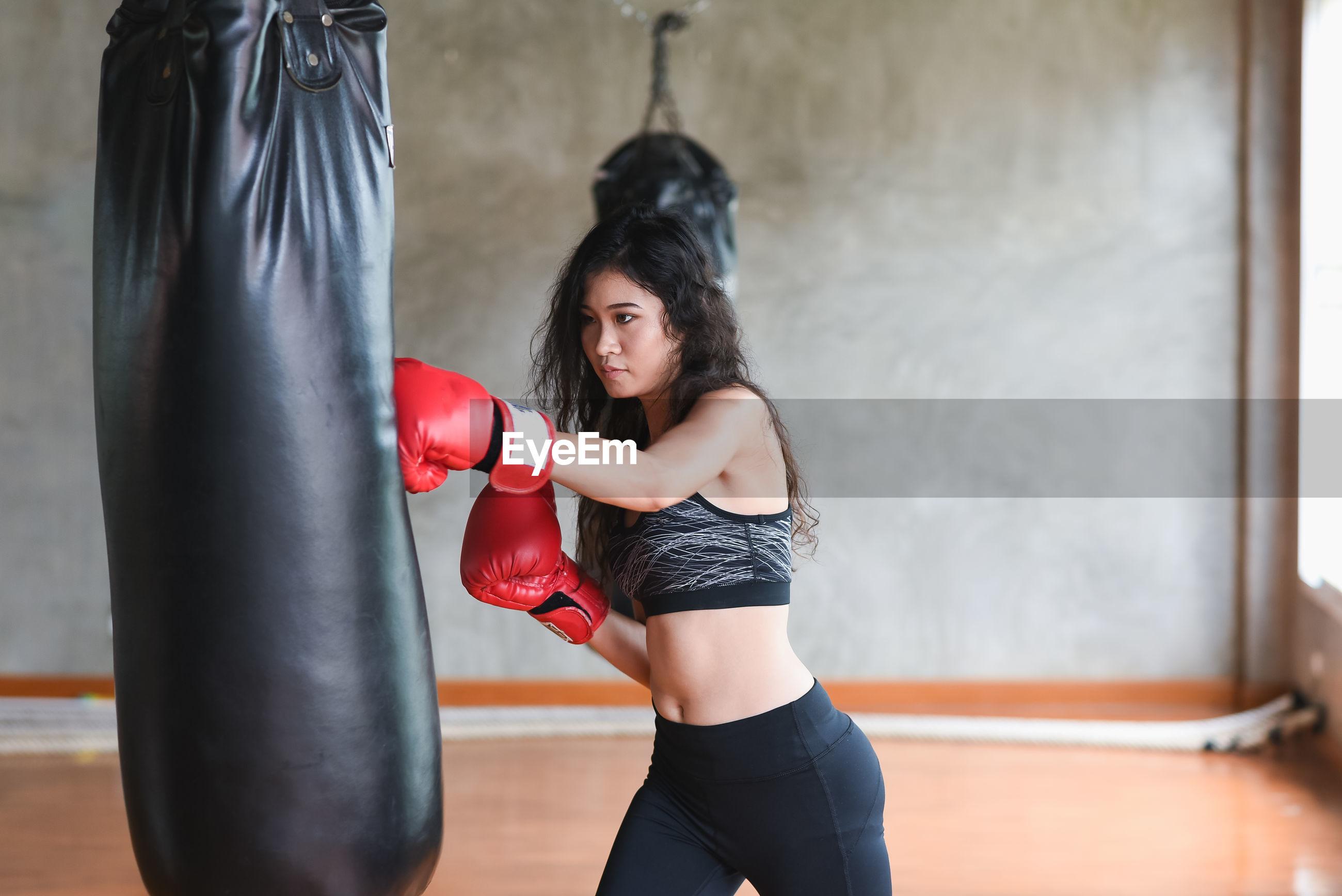 Young woman hitting punching bag in studio