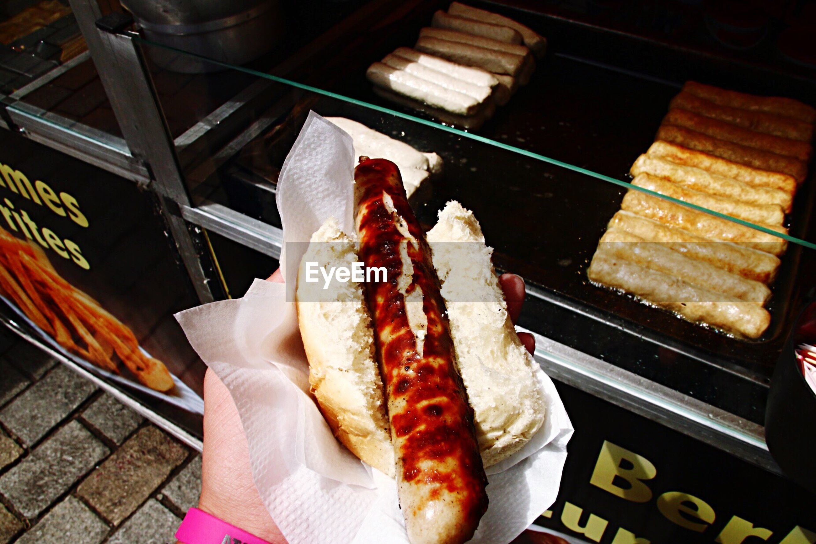 Cropped hand of person holding hot dog