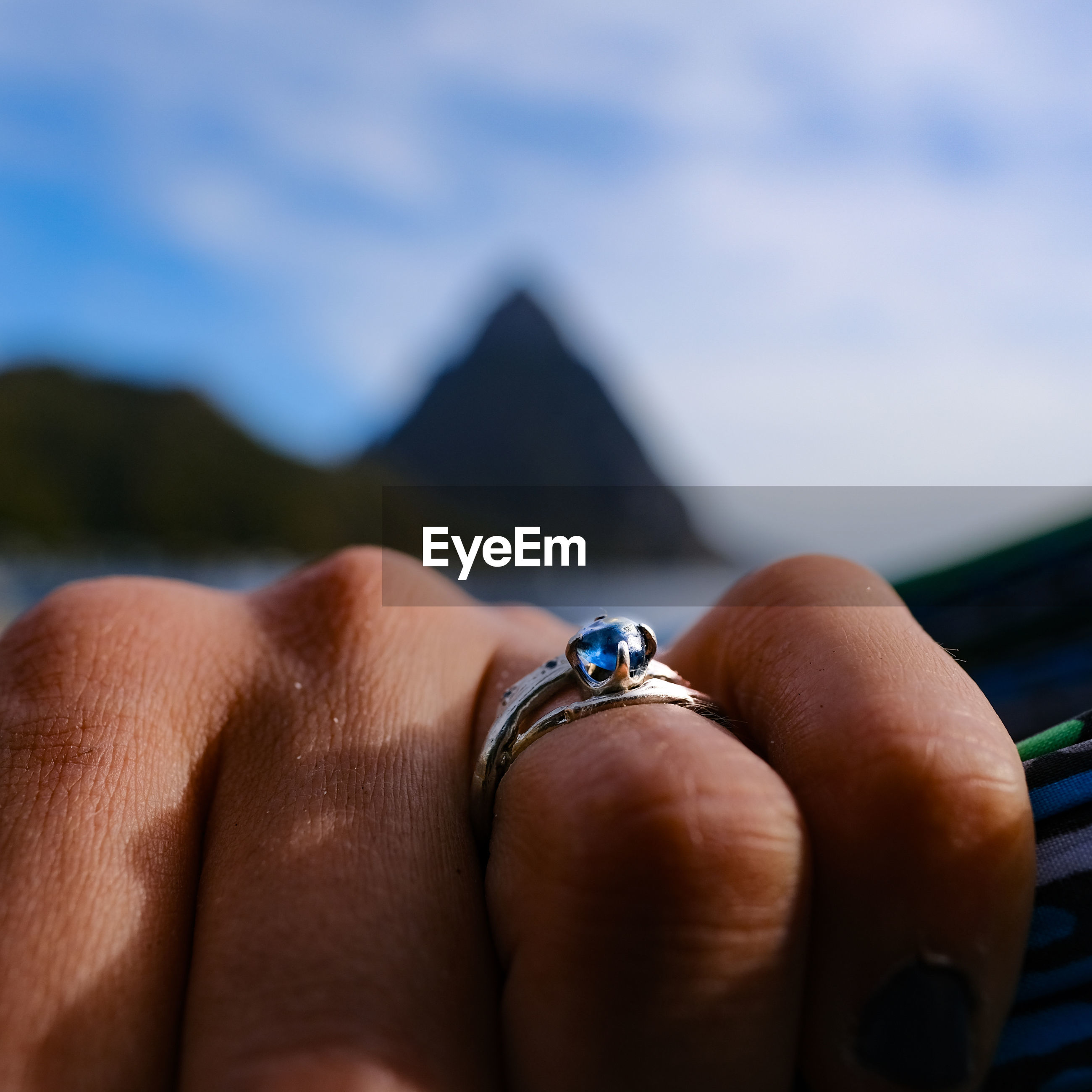 Cropped image of woman hand with ring against sky