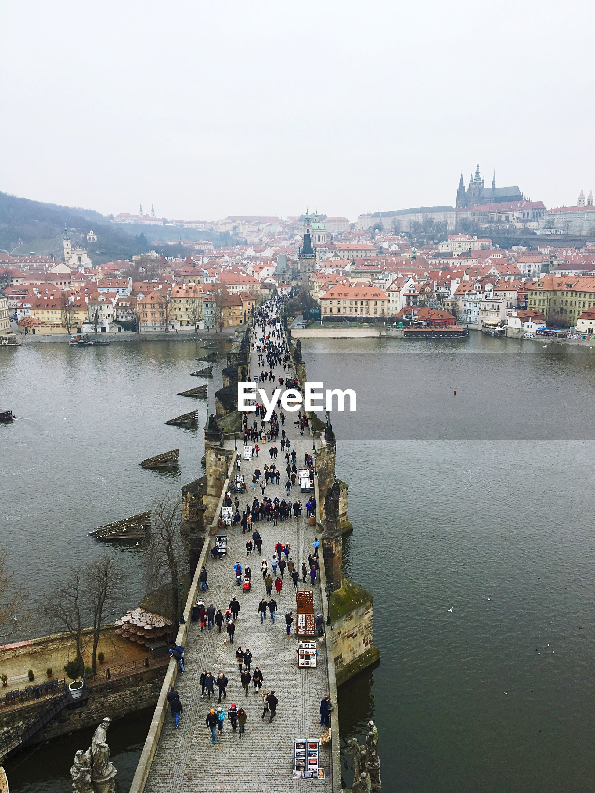 People walking on charles bridge over vltava river by town against clear sky