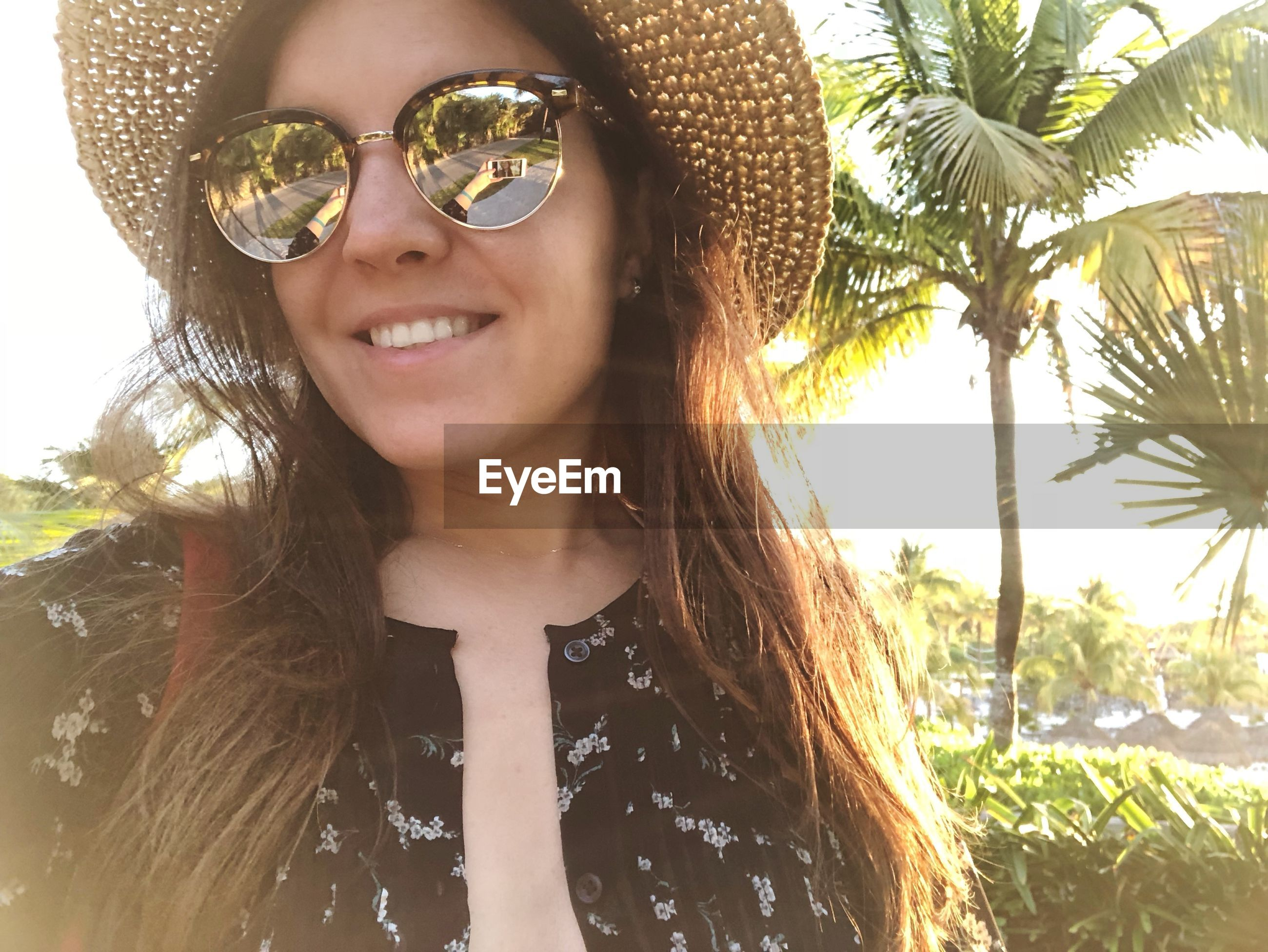 Portrait of smiling young woman in sunglasses and hat against trees