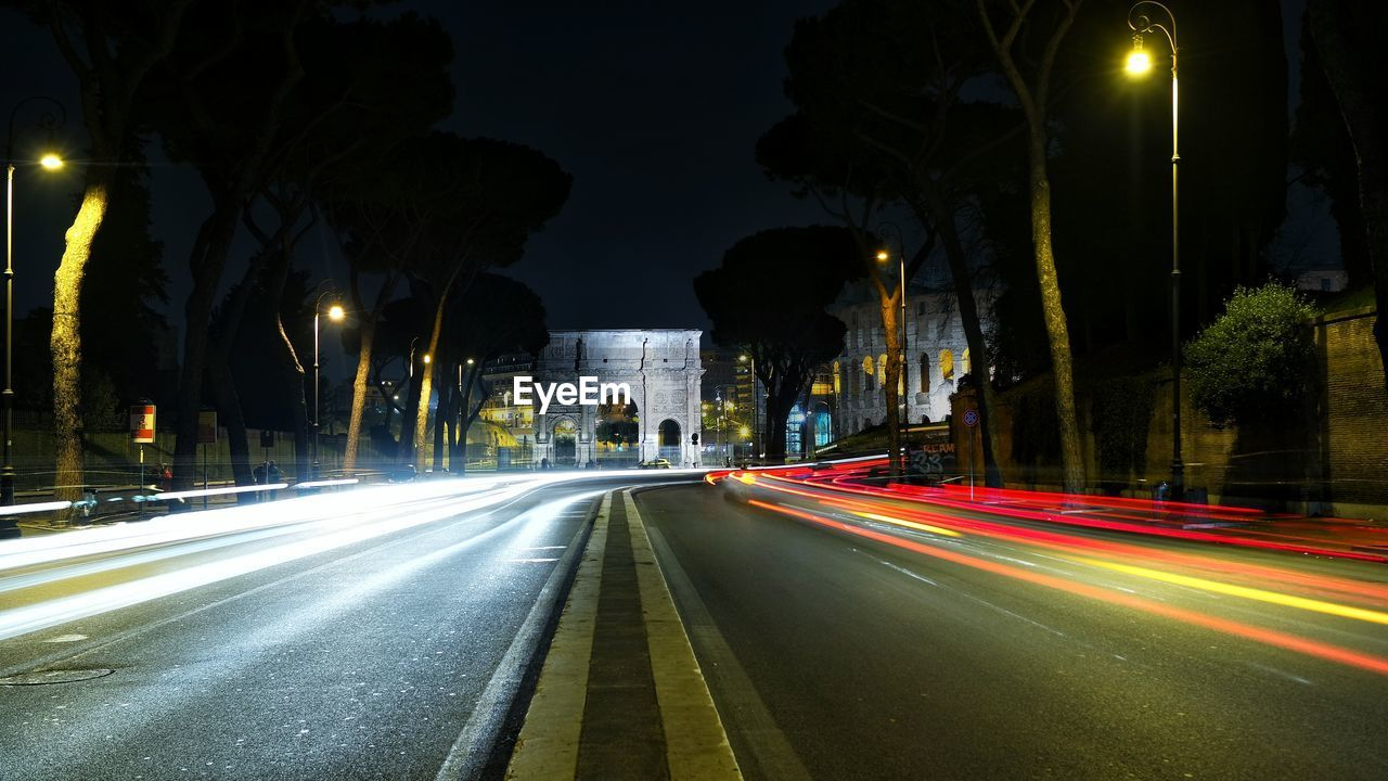 Light trails over street against sky at night