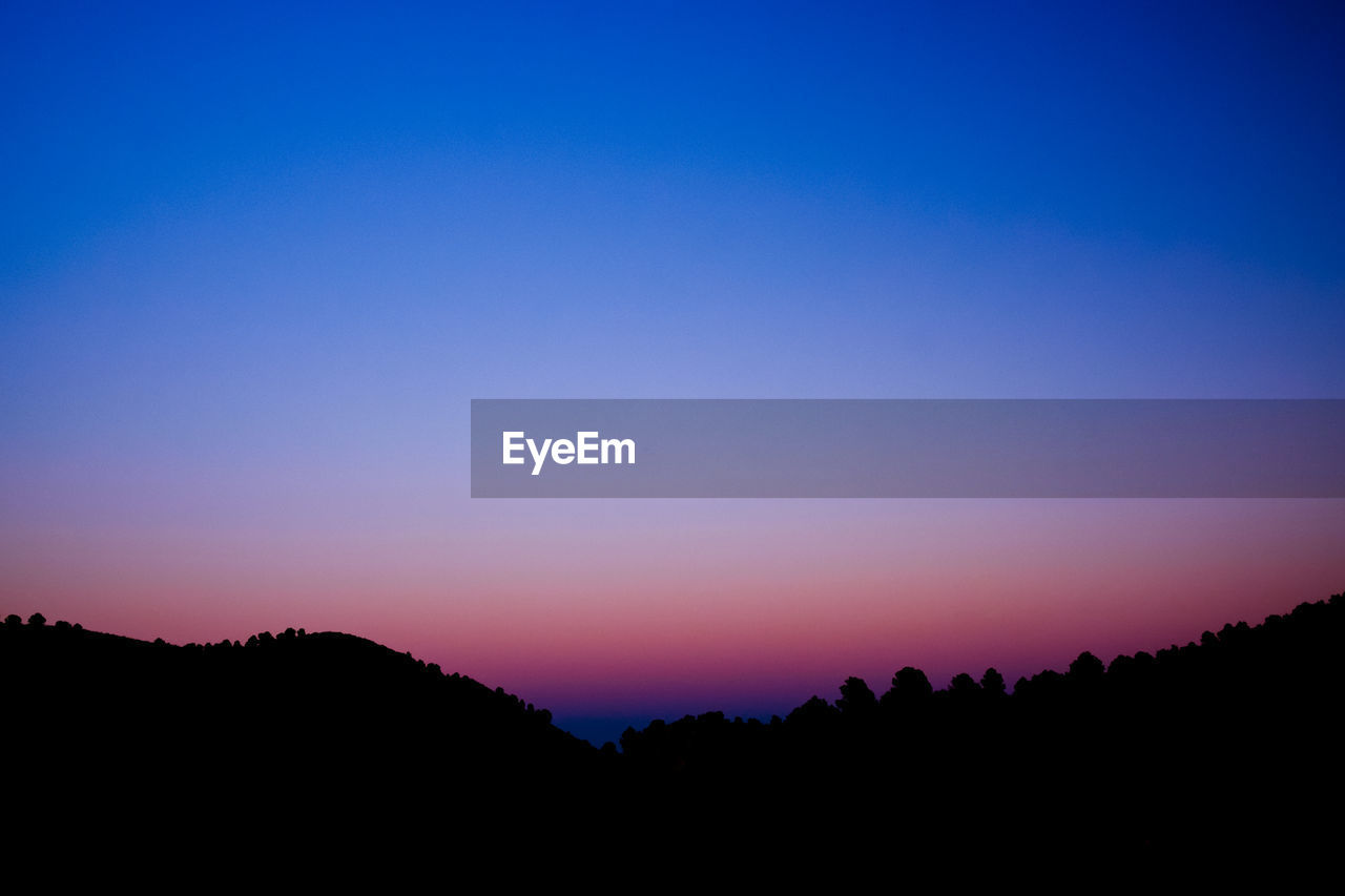 sky, beauty in nature, sunset, tranquility, tranquil scene, silhouette, scenics - nature, copy space, nature, idyllic, mountain, clear sky, no people, landscape, non-urban scene, environment, orange color, tree, outdoors, blue, romantic sky