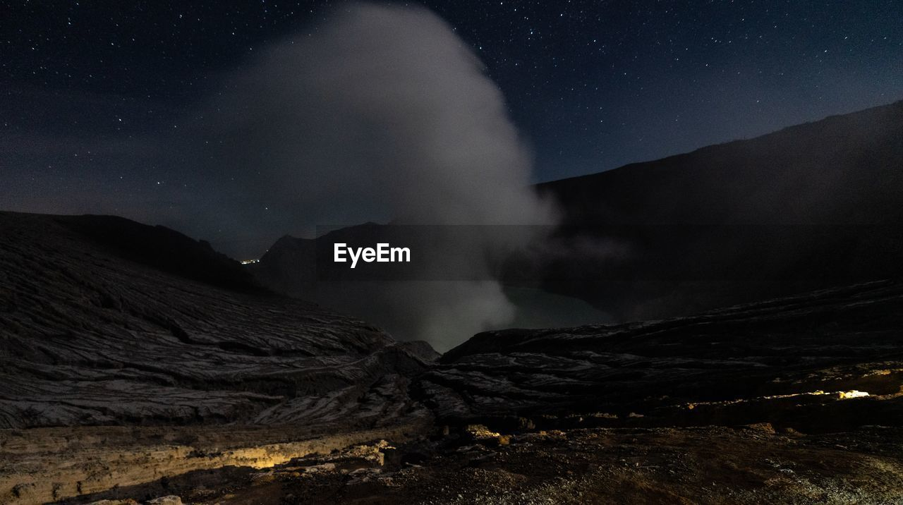 night, scenics - nature, mountain, beauty in nature, non-urban scene, geology, environment, nature, sky, landscape, physical geography, land, star - space, tranquil scene, volcano, heat - temperature, power in nature, erupting, no people, smoke - physical structure, outdoors, volcanic crater