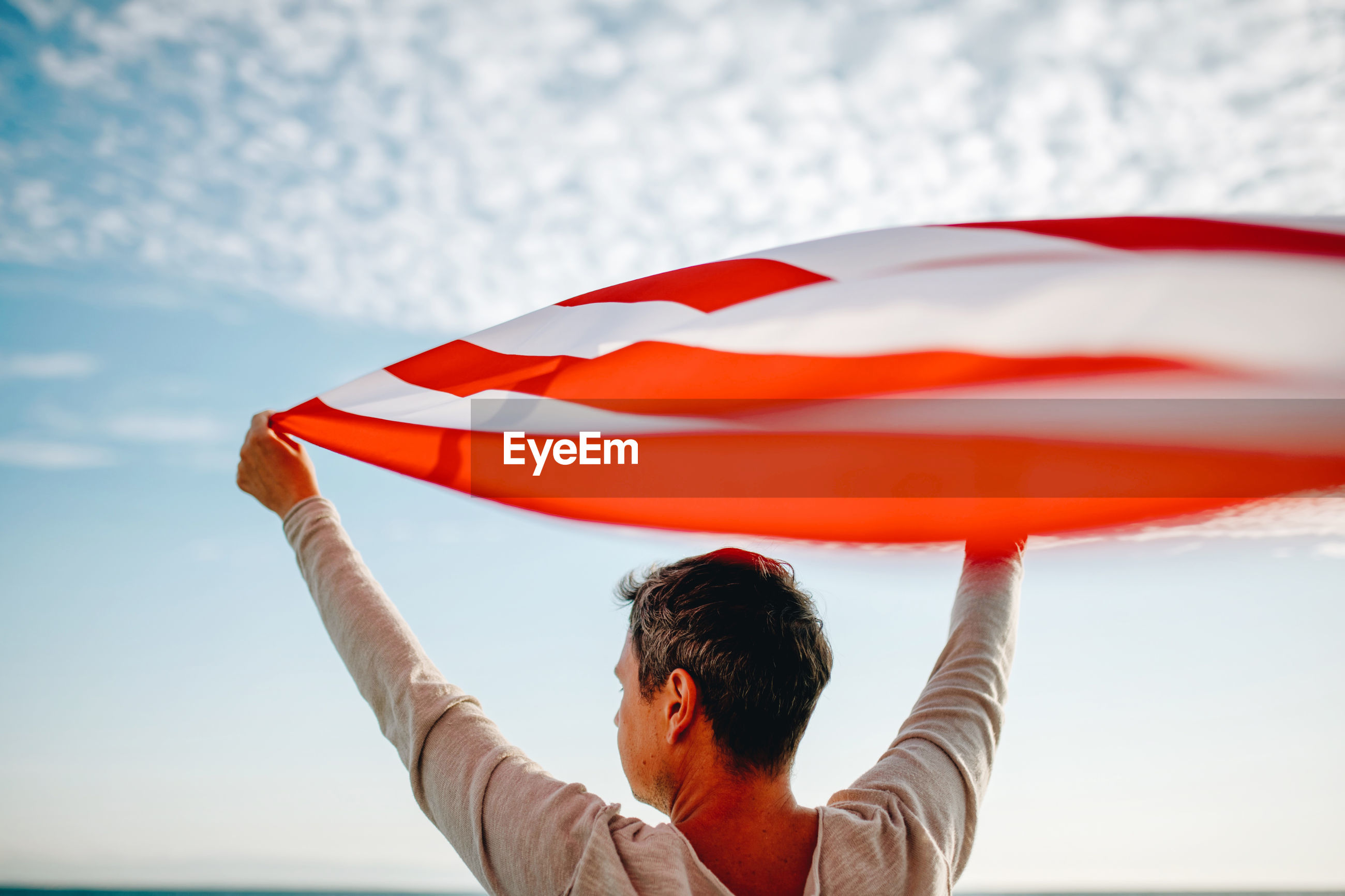 Rear view of man holding american flag against sky