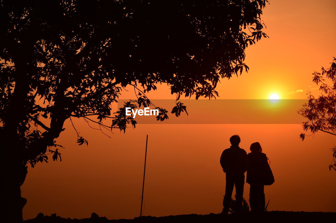 Silhouette couple on land against sky during sunset