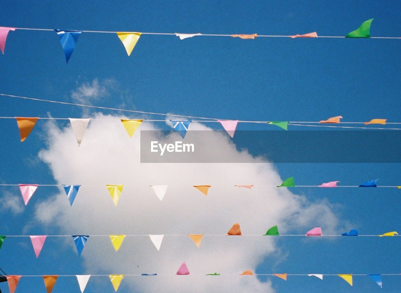 hanging, blue, sky, bunting, decoration, multi colored, flag, low angle view, celebration, no people, cloud - sky, day, nature, string, wind, environment, in a row, outdoors, side by side, streamer