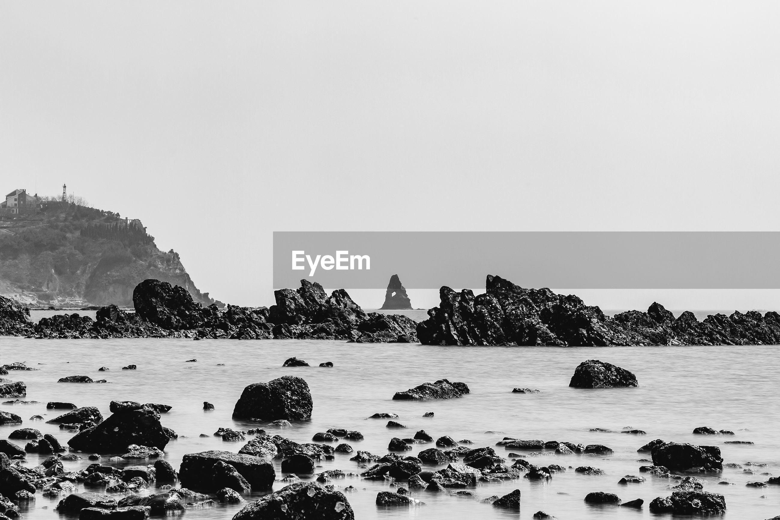 Rocks at seashore against clear sky