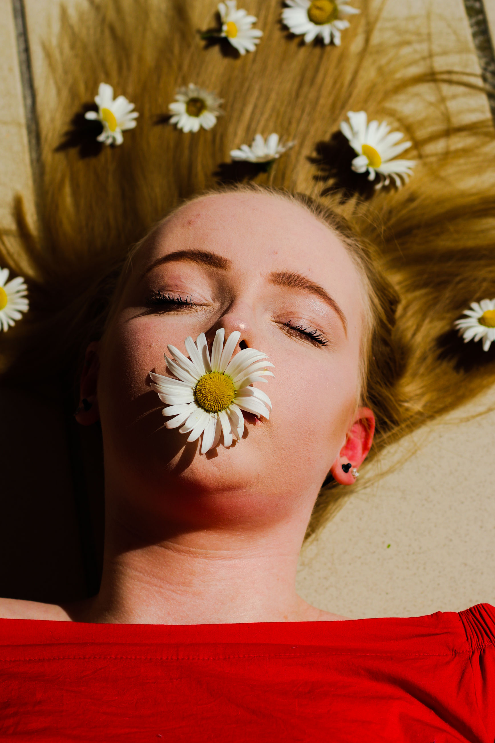 Close-up of woman with flowers lying down on bed