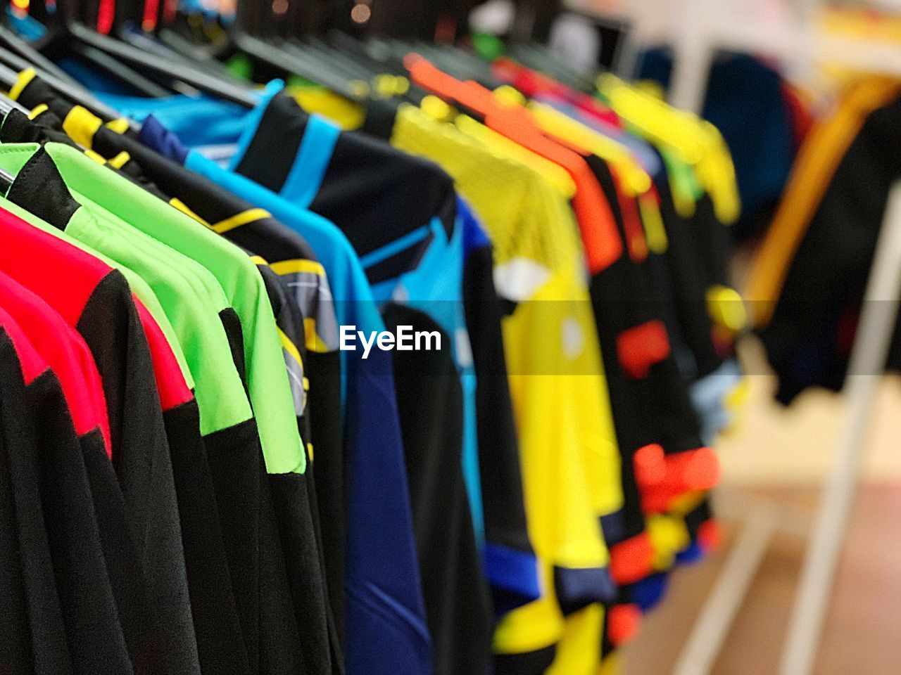 multi colored, variation, choice, focus on foreground, no people, in a row, close-up, clothing, large group of objects, indoors, rack, side by side, retail, store, arrangement, collection, hanging, clothes rack, selective focus, coathanger, consumerism