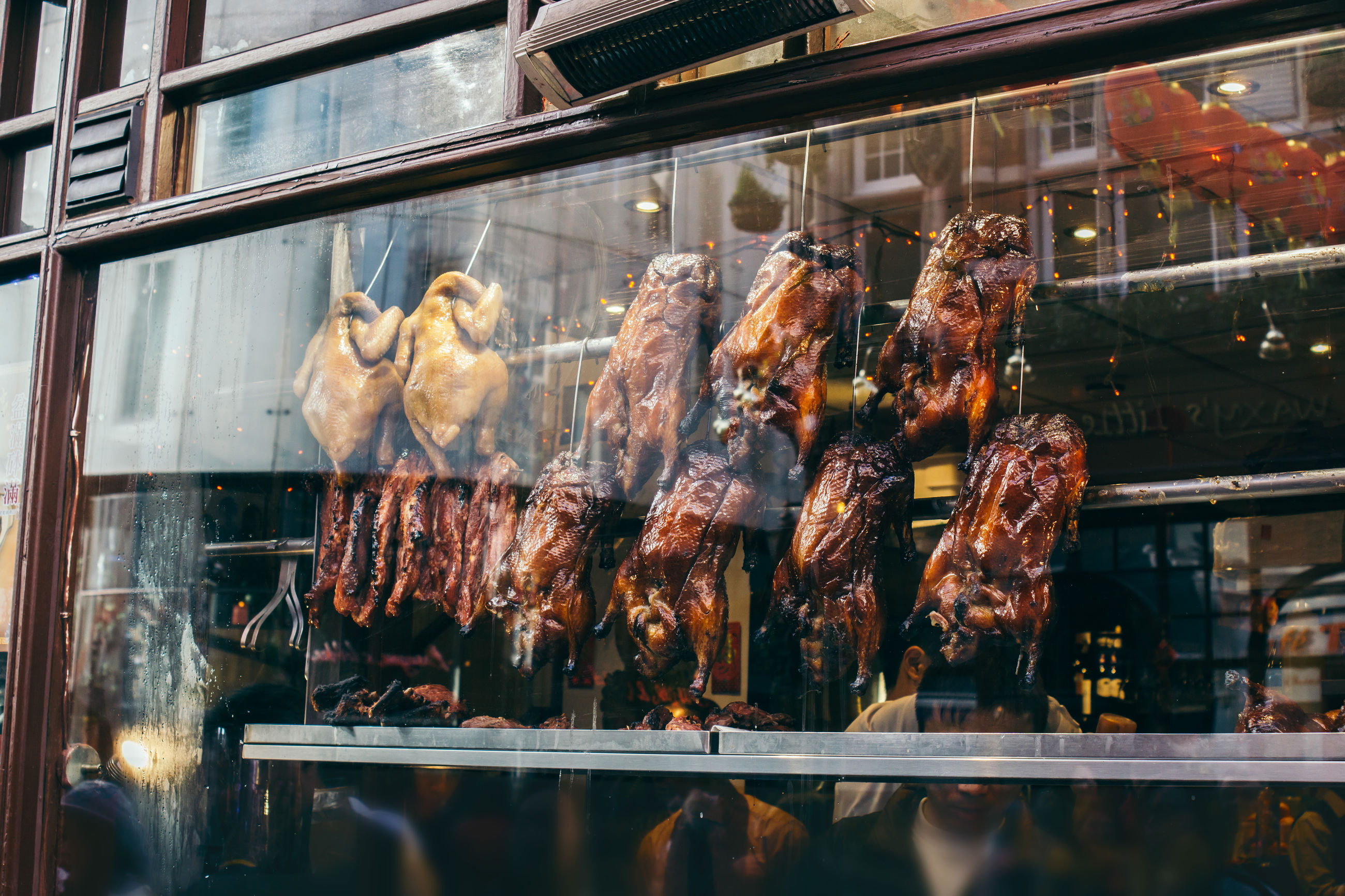 Low angle view of meat hanging in store seen through window