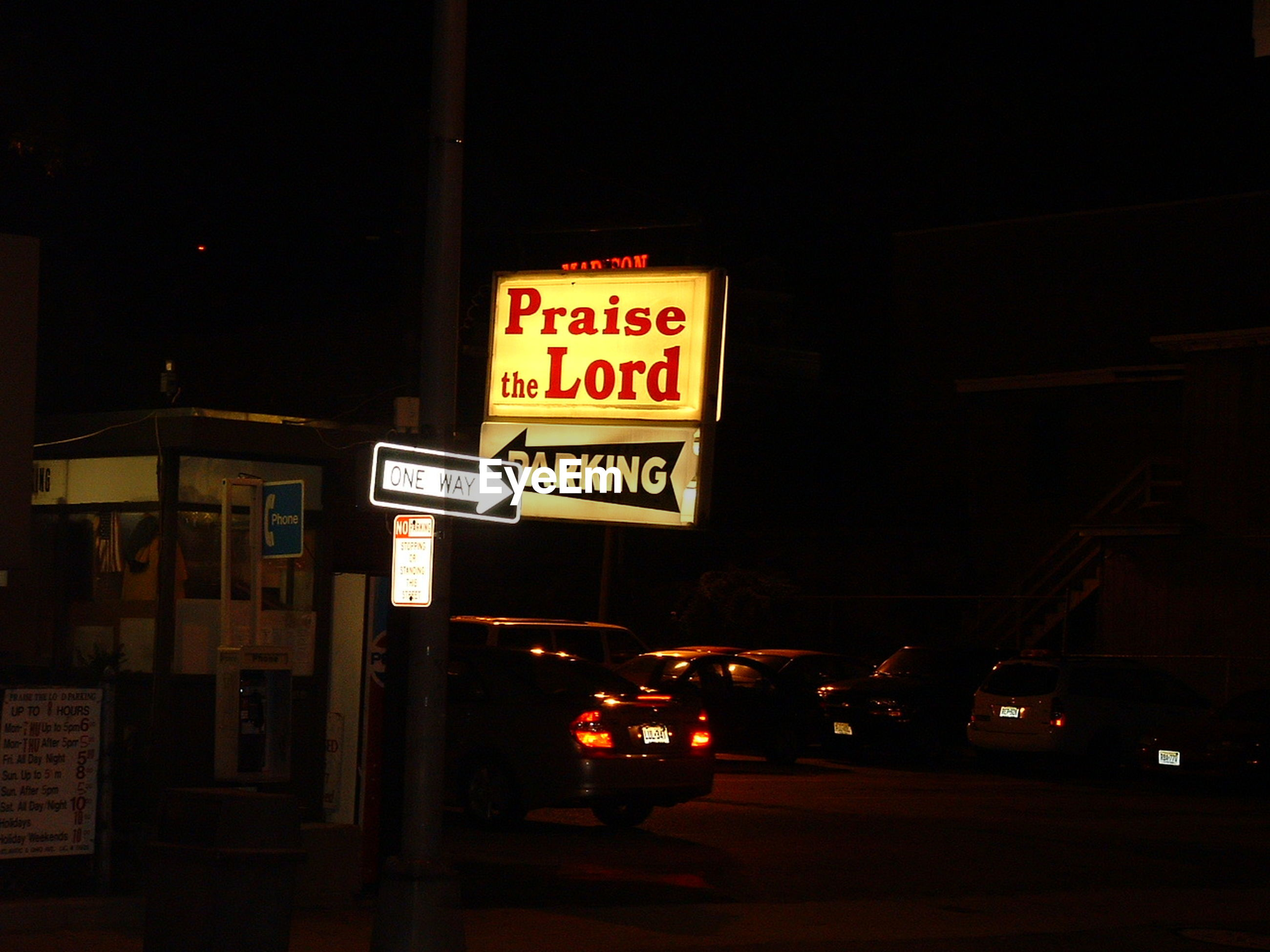 INFORMATION SIGN ON ILLUMINATED STREET LIGHT AT NIGHT