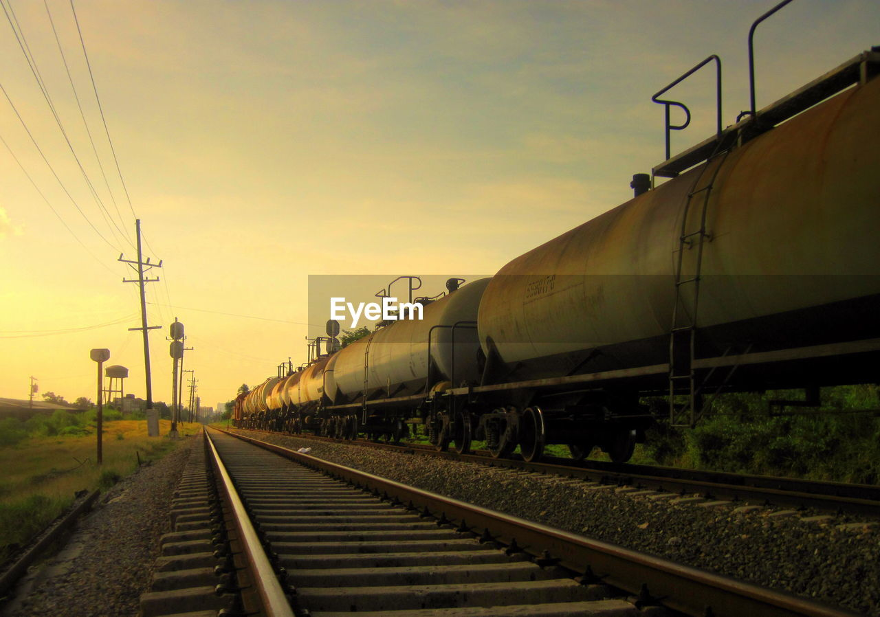 railroad track, transportation, rail transportation, train - vehicle, mode of transport, freight transportation, sky, sunset, cable, public transportation, outdoors, electricity pylon, no people, electricity, day, locomotive