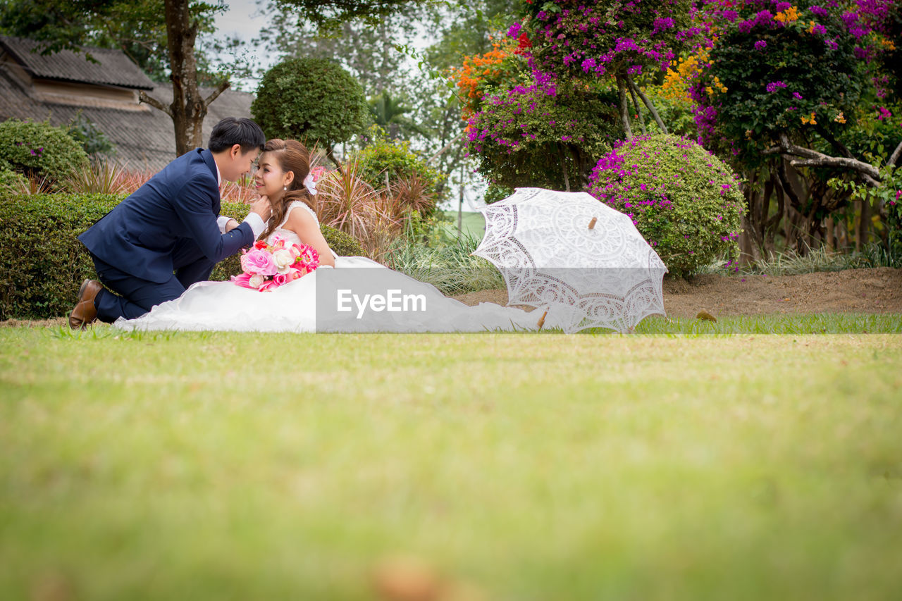 Newlywed Couple Romancing On Grassy Field At Public Park