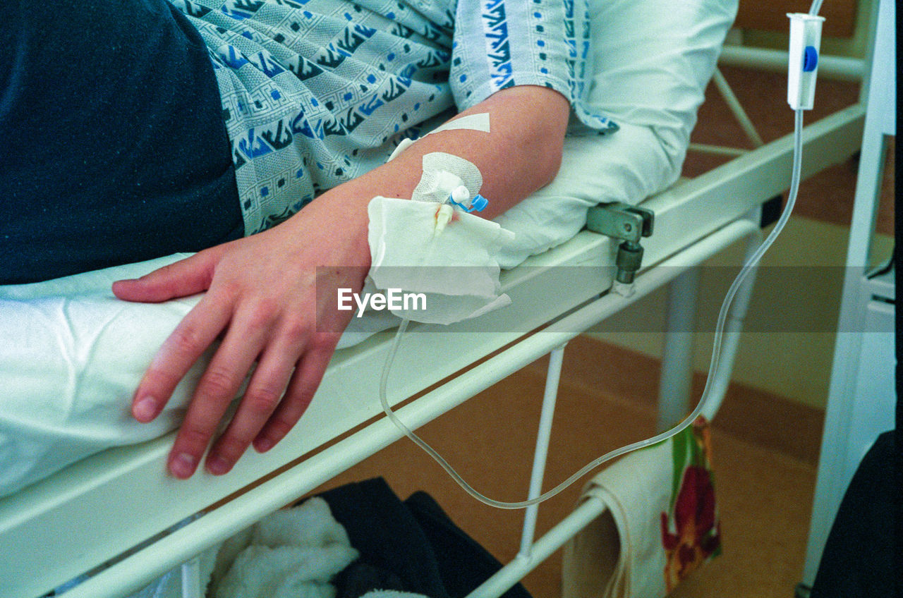 Midsection Of Man Lying On Hospital Bed