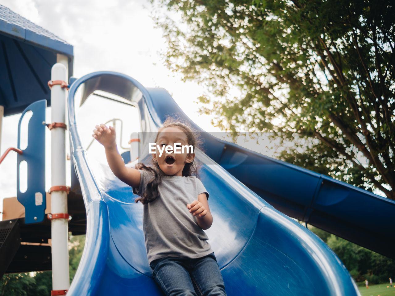 Cute girl standing on slide at park