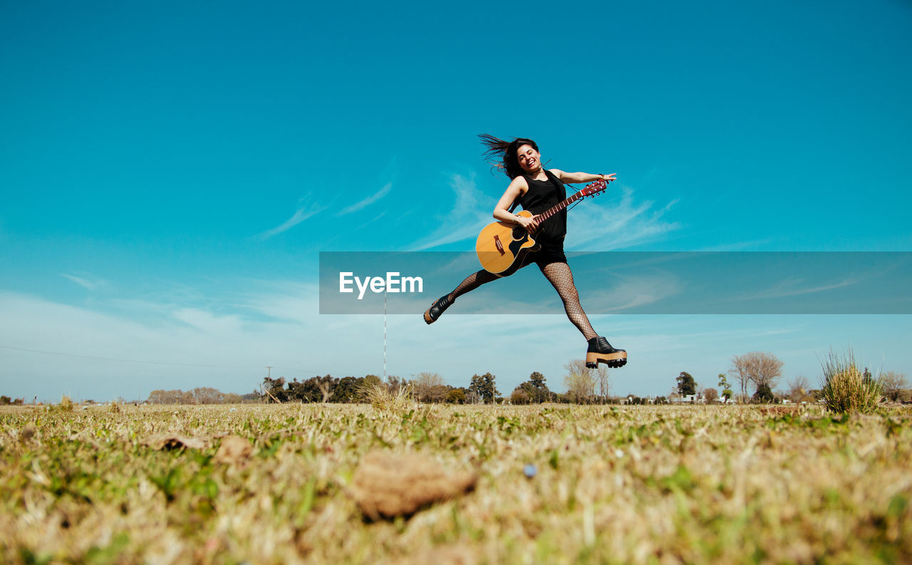 Woman With Guitar Jumping Over Field Against Sky