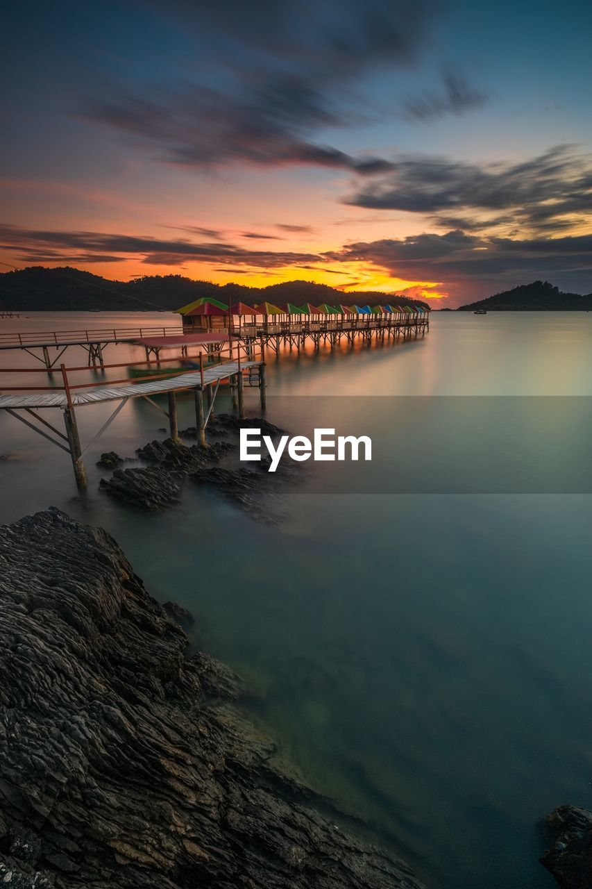 sky, water, sunset, cloud - sky, scenics - nature, beauty in nature, nature, tranquility, tranquil scene, orange color, rock, built structure, no people, architecture, idyllic, rock - object, sea, reflection, solid, outdoors