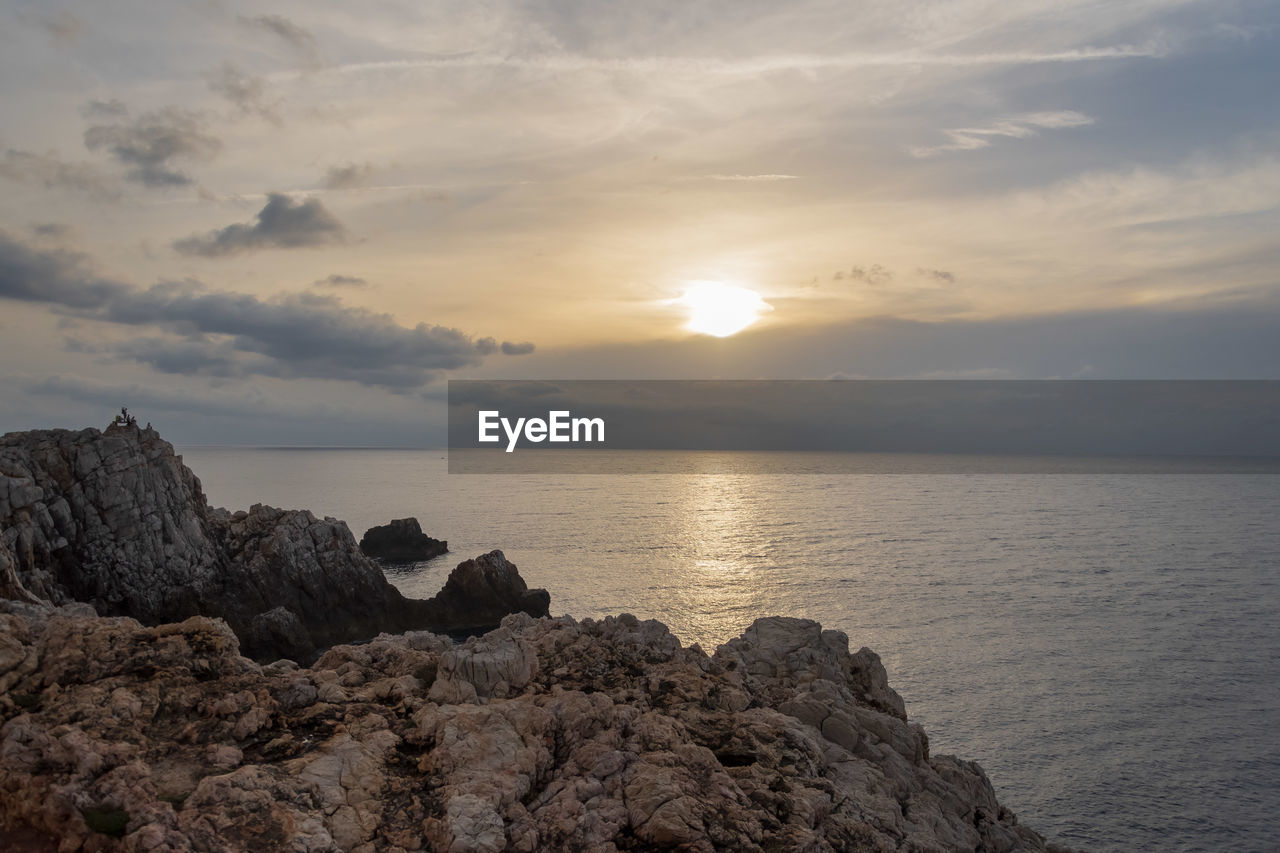 sky, sea, water, sunset, beauty in nature, scenics - nature, cloud - sky, horizon, horizon over water, tranquility, rock, sun, tranquil scene, solid, rock - object, nature, idyllic, no people, land, outdoors