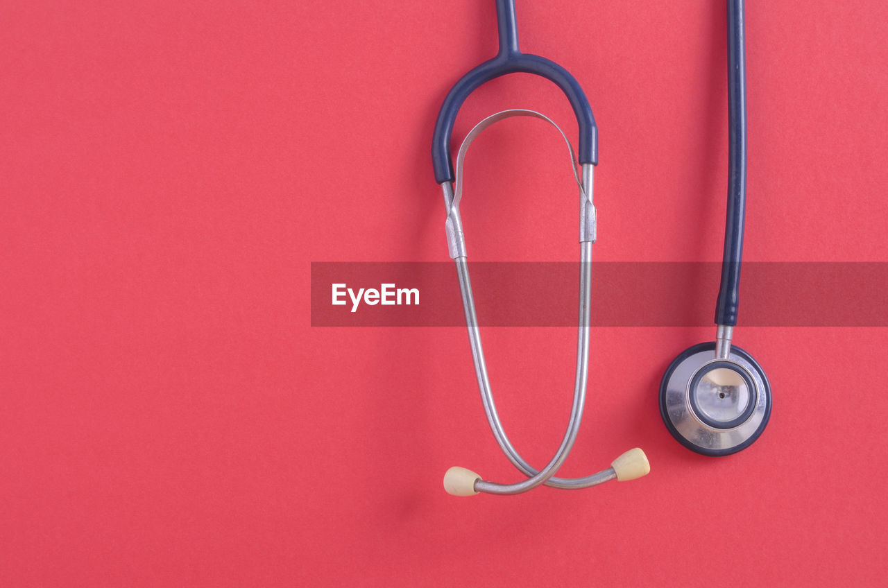stethoscope, medical instrument, medical equipment, medical supplies, red, indoors, healthcare and medicine, no people, diagnostic medical tool, still life, close-up, medical exam, occupation, connection, listening, copy space, hospital, metal, responsibility, care, pulse trace