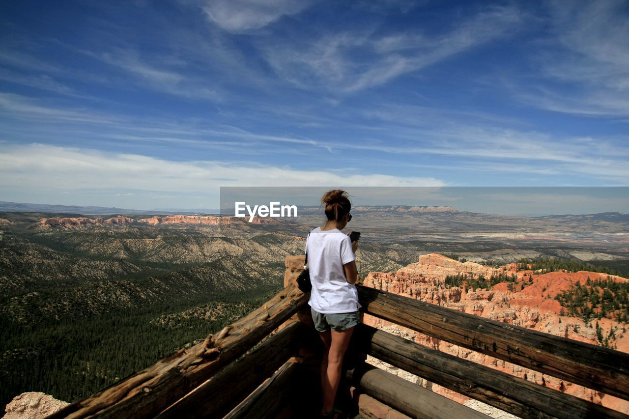 Rear view of woman looking at mountains against blue sky