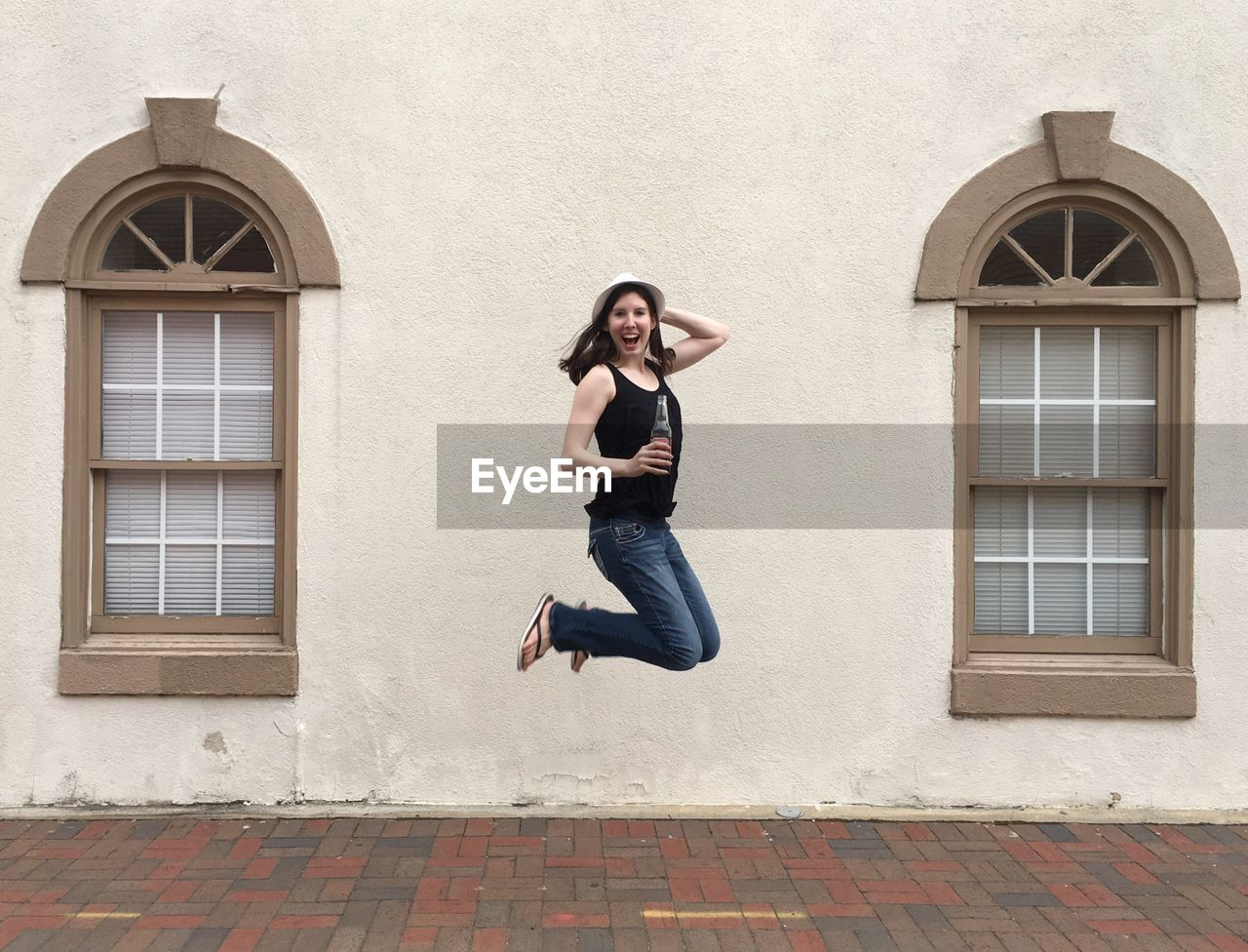 Portrait Of Happy Woman Jumping Against Wall