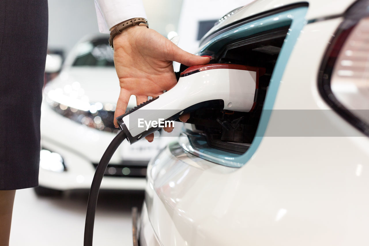 Cropped Hand Of Woman Filling Fuel In Car