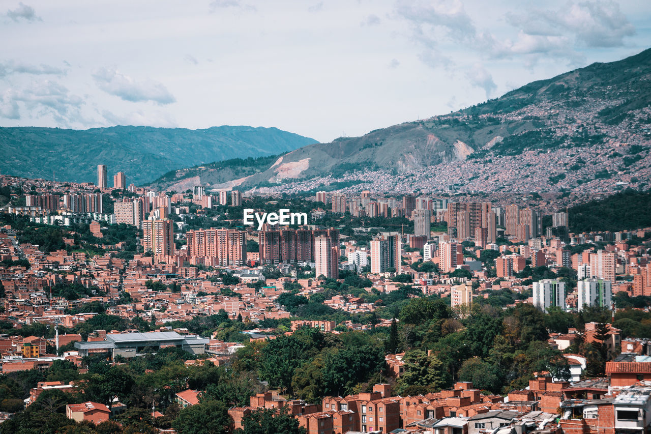 mountain, architecture, building exterior, city, built structure, sky, residential district, mountain range, building, nature, crowd, outdoors, day, crowded, tree, cityscape, high angle view, cloud - sky, town, townscape