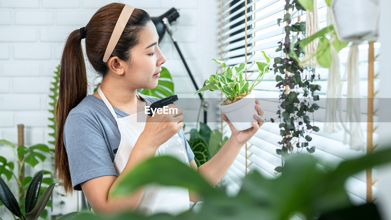 PORTRAIT OF WOMAN HOLDING POTTED PLANT