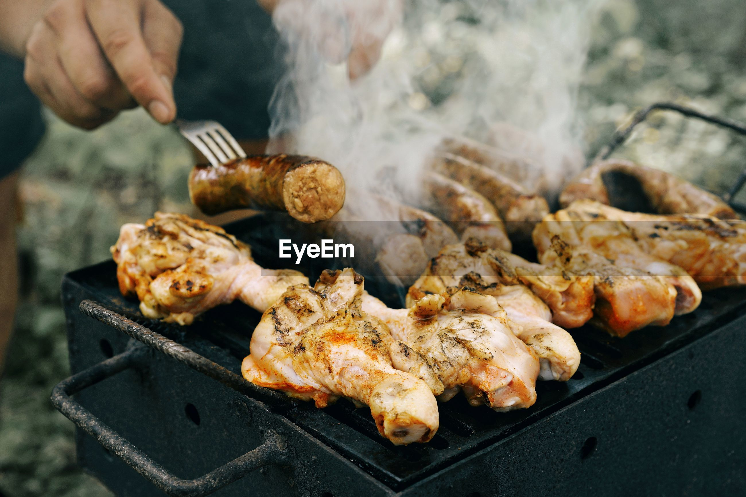 Cropped image of man grilling meat on barbecue grill