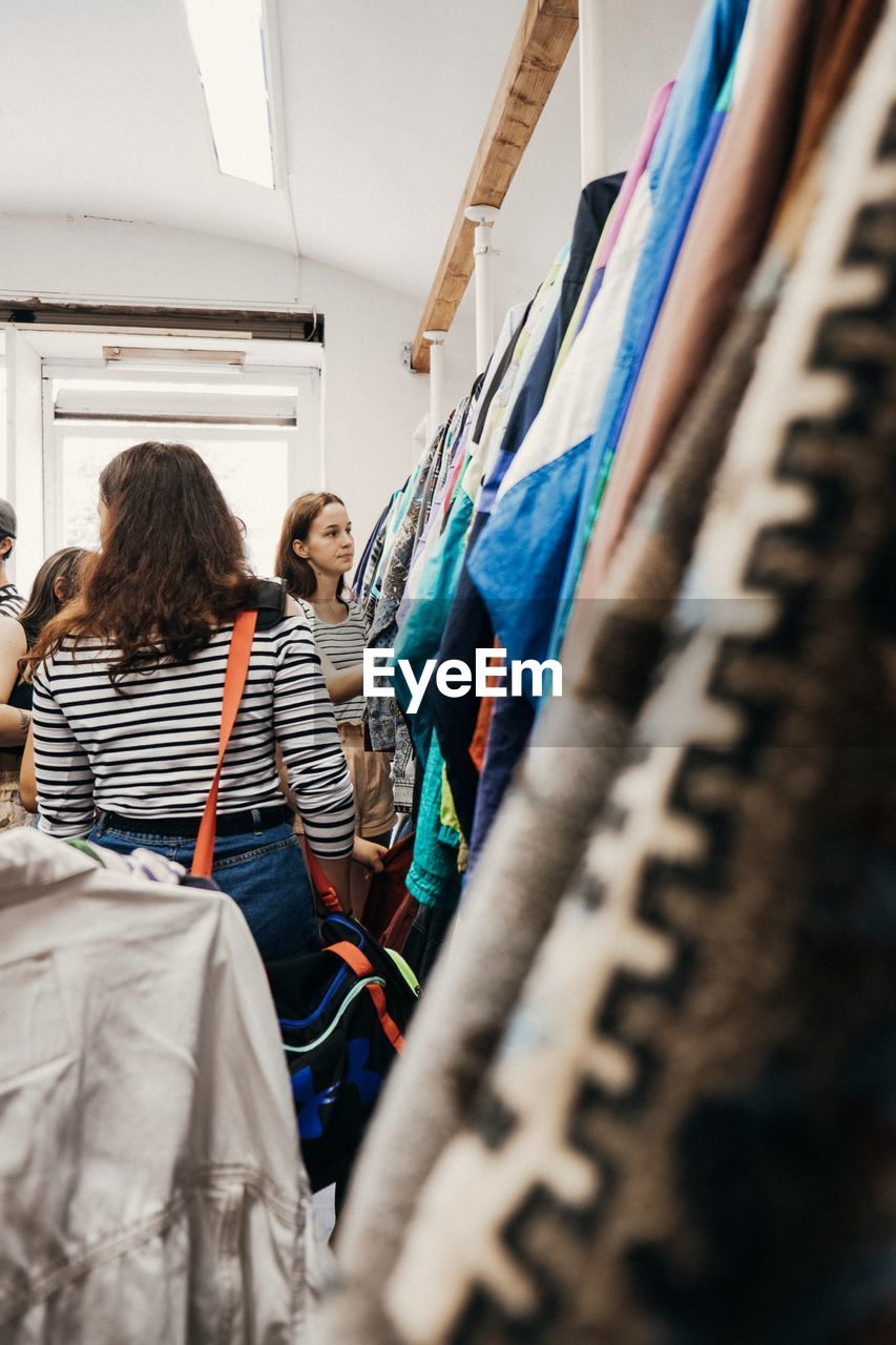 real people, women, selective focus, indoors, casual clothing, people, rear view, standing, adult, clothing, togetherness, lifestyles, two people, communication, small business, young women, choice, textile, retail, young adult, hairstyle