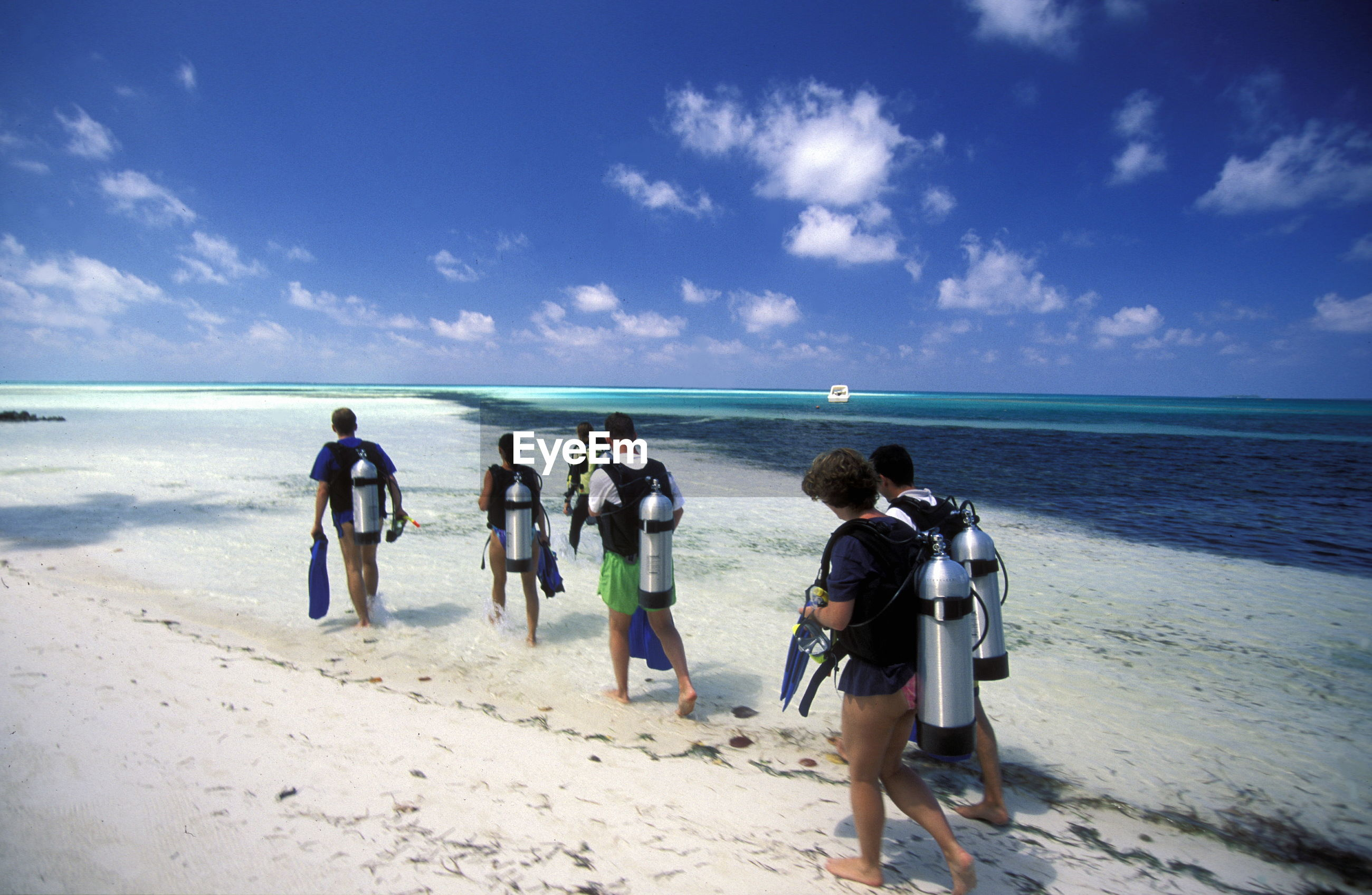 Rear view of scuba divers wearing aqualung walking on sand at beach against sky