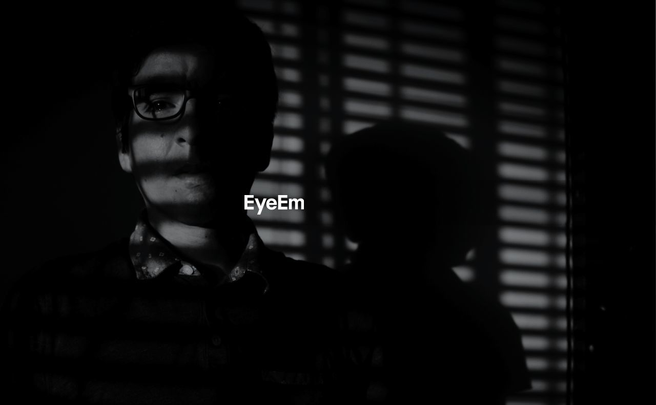 Man Standing In Darkroom