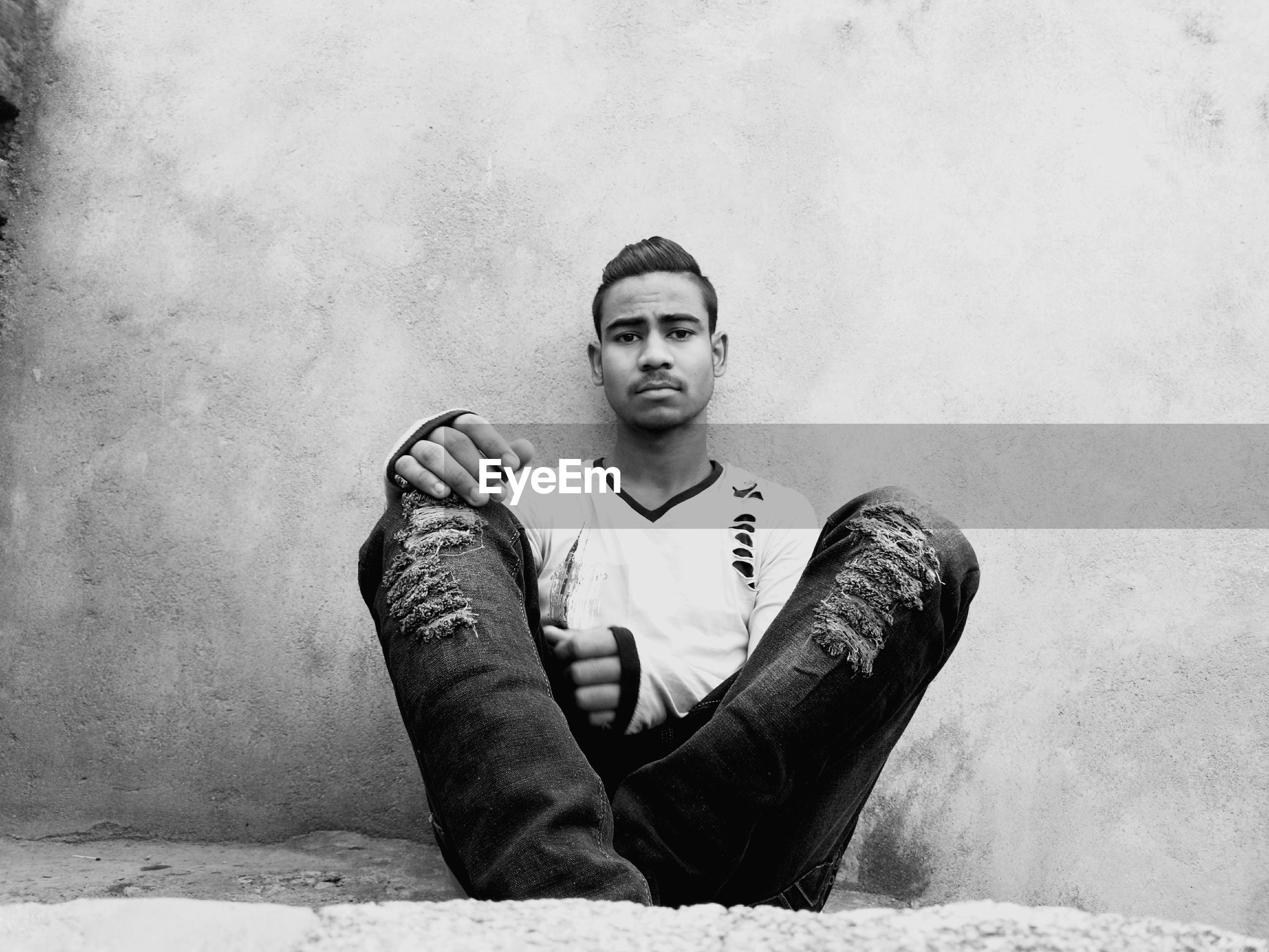 Young man sitting against wall