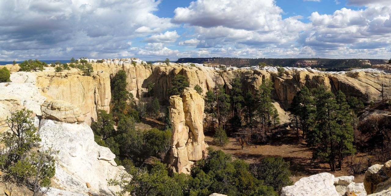 sky, rock, cloud - sky, environment, nature, landscape, rock formation, rock - object, cliff, land, travel, beauty in nature, solid, scenics - nature, water, scenery, urban skyline, outdoors, non-urban scene, mountain, formation, high, eroded