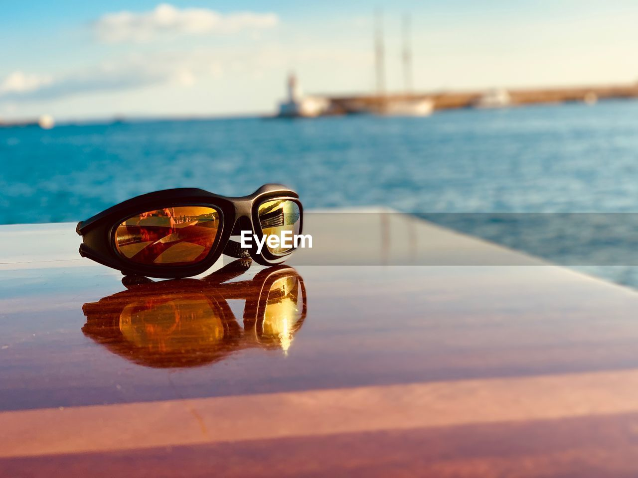water, glasses, sea, sunglasses, reflection, fashion, sky, nature, beach, land, sunlight, no people, scenics - nature, cloud - sky, day, close-up, security, focus on foreground, outdoors, personal accessory, horizon over water, eyewear