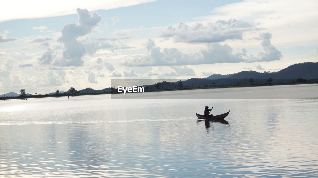 water, sky, cloud - sky, nautical vessel, transportation, waterfront, mode of transportation, beauty in nature, tranquil scene, scenics - nature, tranquility, nature, lake, real people, one person, day, men, non-urban scene, leisure activity, outdoors, rowing