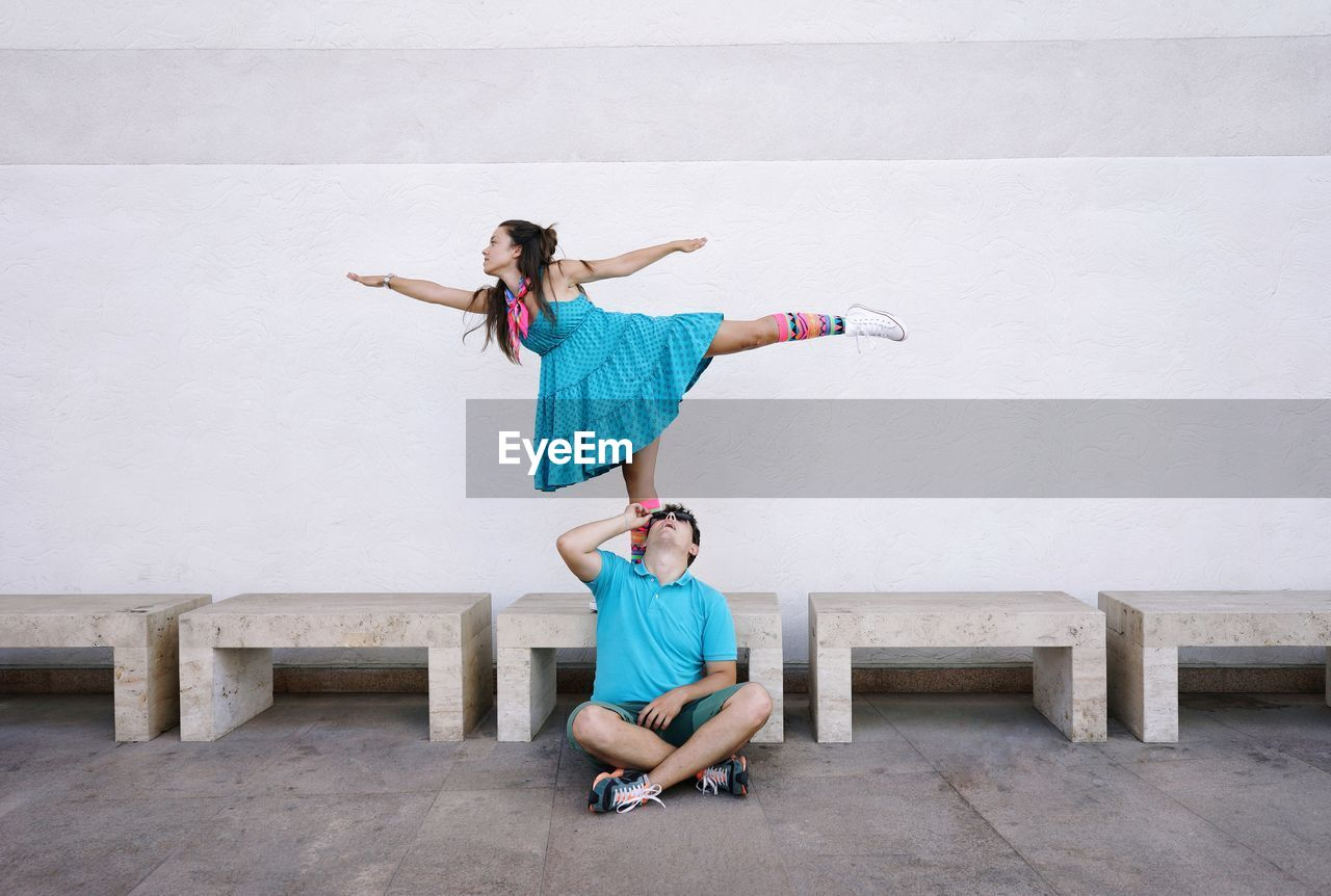Man sitting by woman dancing against wall