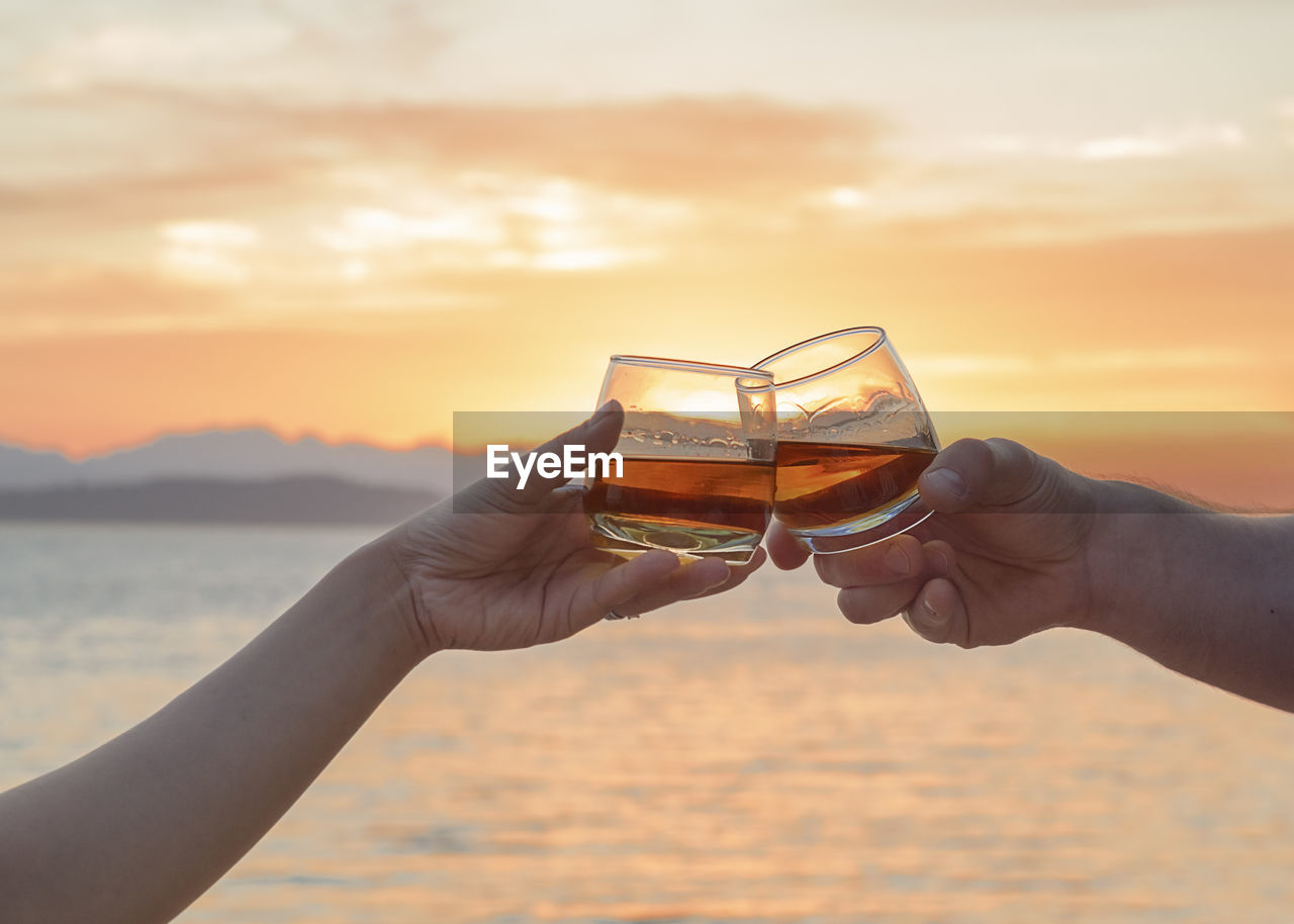 Cropped Hands Of Couple Toasting Glasses At Beach Against Orange Sky