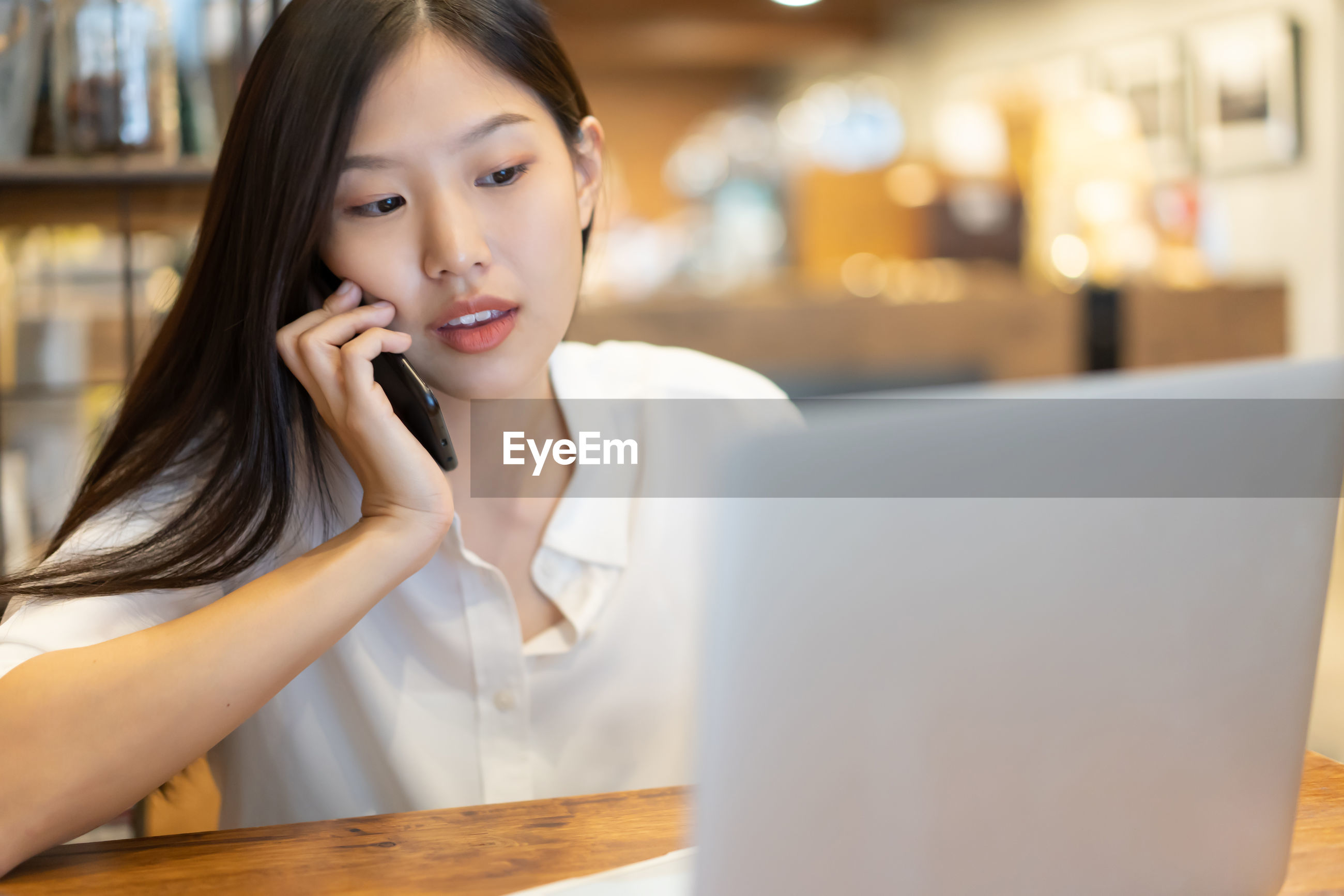 Woman talking on mobile phone while using laptop at home