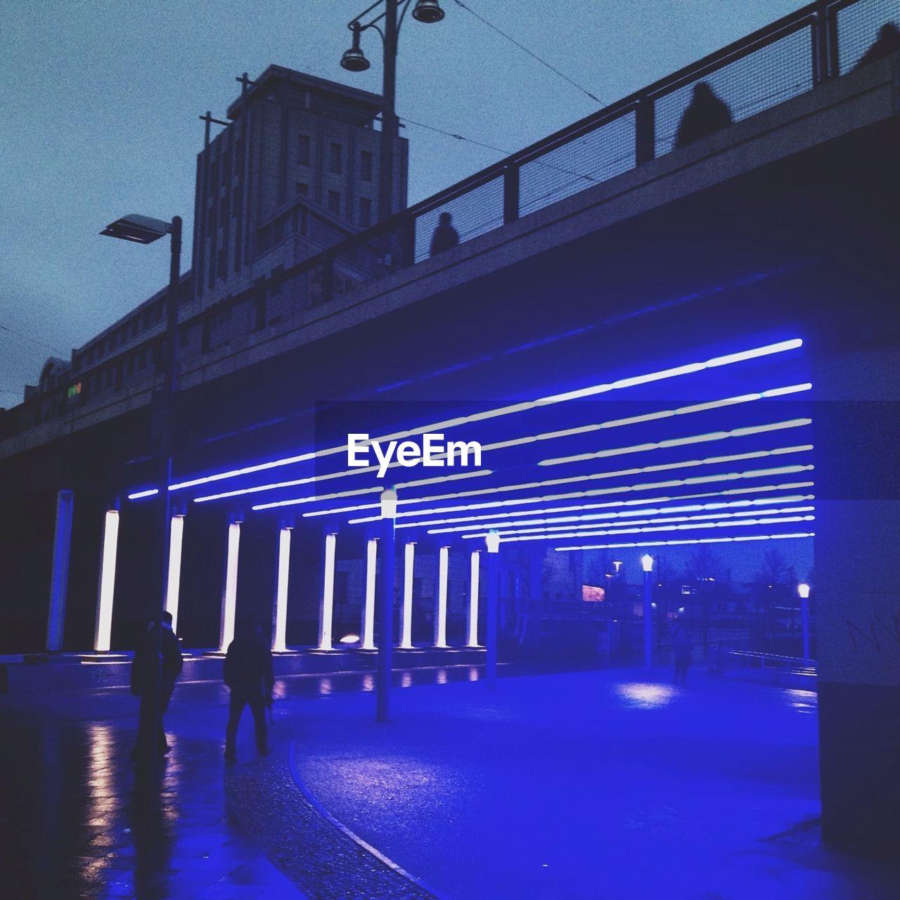 Illuminated blue light fixtures below bridge in city
