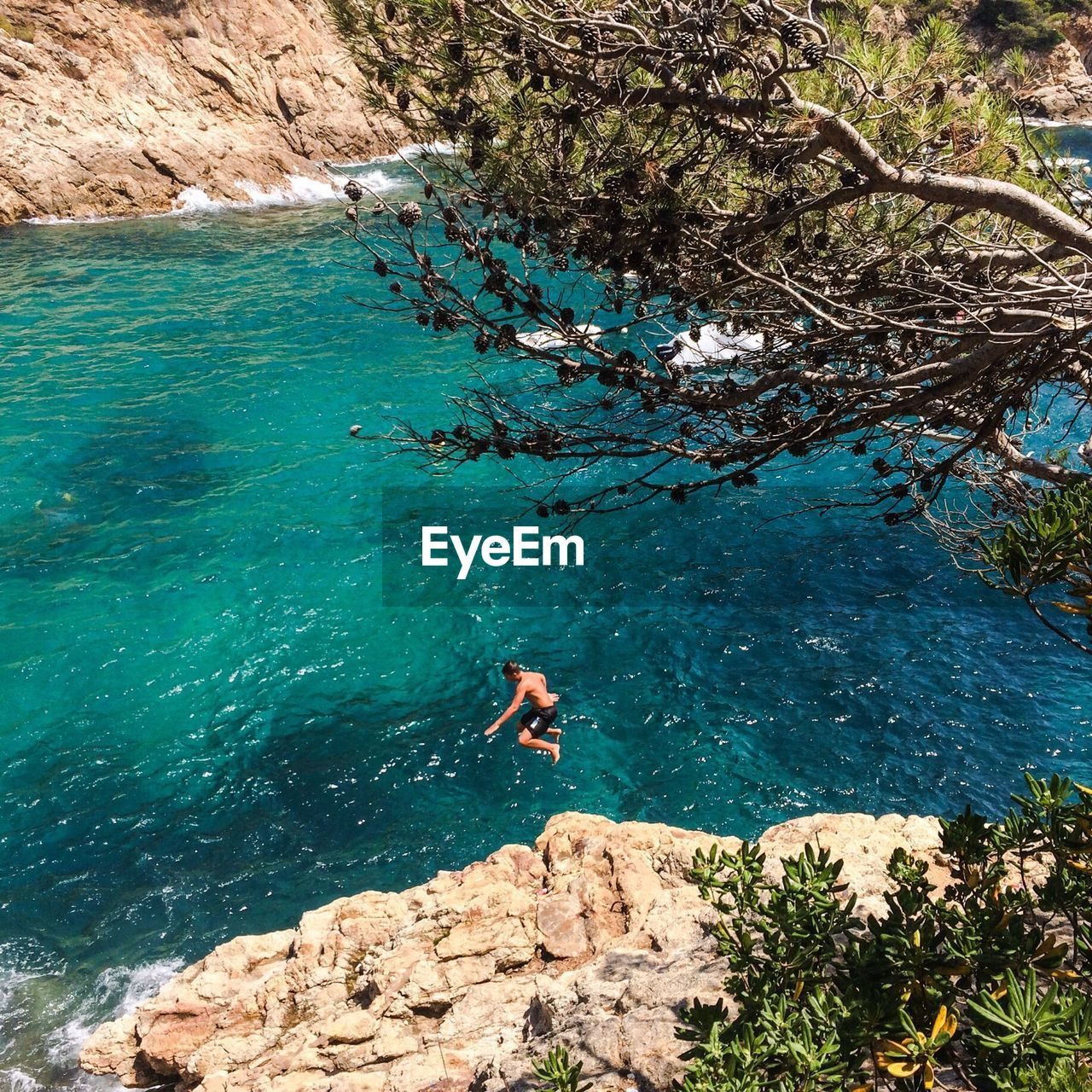 High angle view of man jumping in river by cliff