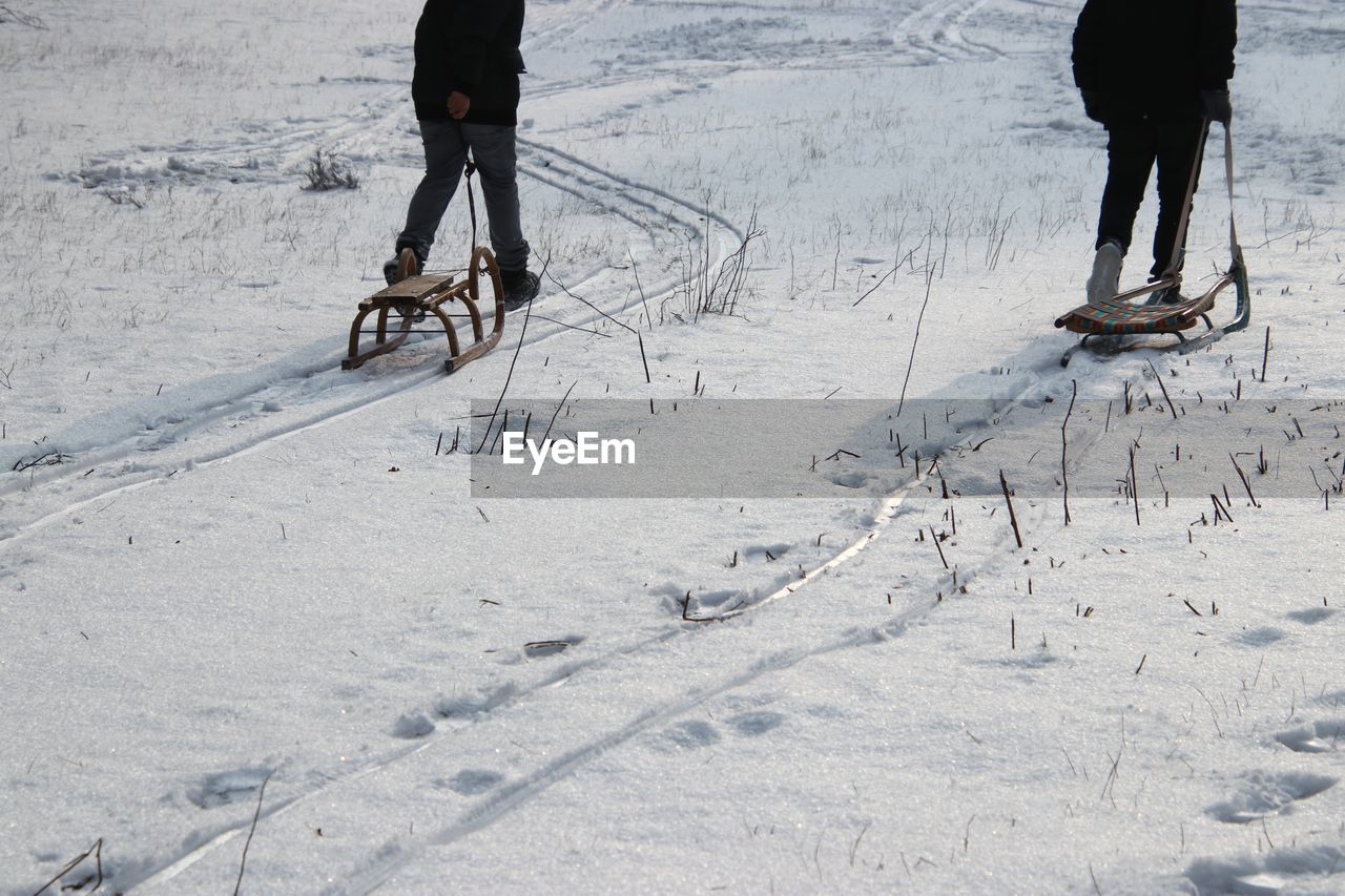 Low section of people with sleds on snow covered land