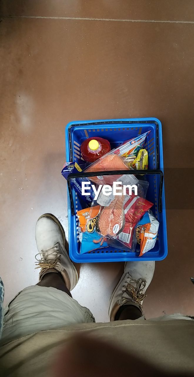 low section, human leg, one person, human body part, body part, personal perspective, real people, shoe, standing, high angle view, lifestyles, men, container, indoors, directly above, blue, casual clothing, box, adult, human foot, jeans, lunch box, human limb