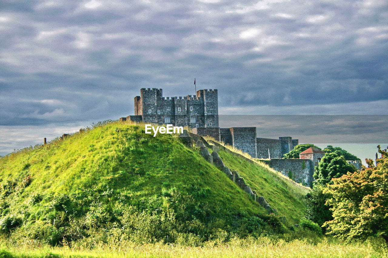 Low angle view of castle on mountain against cloudy sky at dover