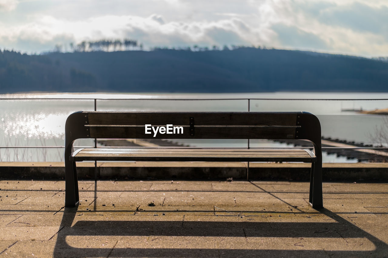 bench, empty, absence, no people, sunlight, river, nature, water, day, outdoors, sky, beauty in nature